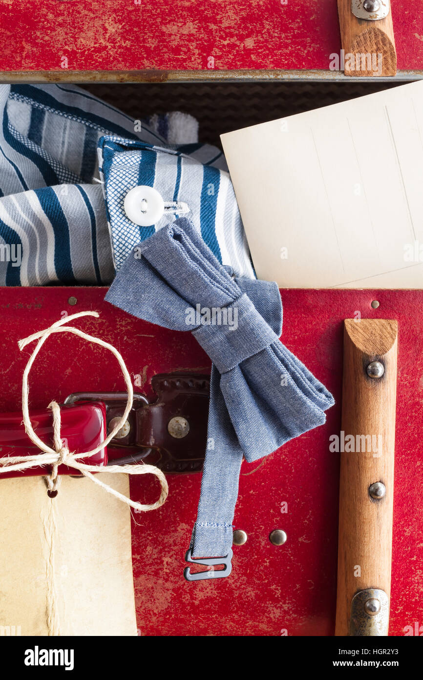 Detail of a vintage suitcase with tag and several objects of a man or boy at a journey: bow tie, pajama and postcard - Stock Image