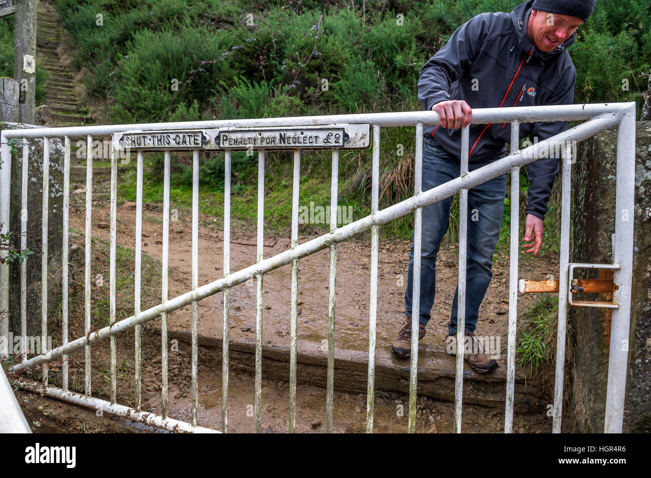 Man opening a white metal gate with sign 'shut this gate' , 'penalty for neglect £2' - Stock Image