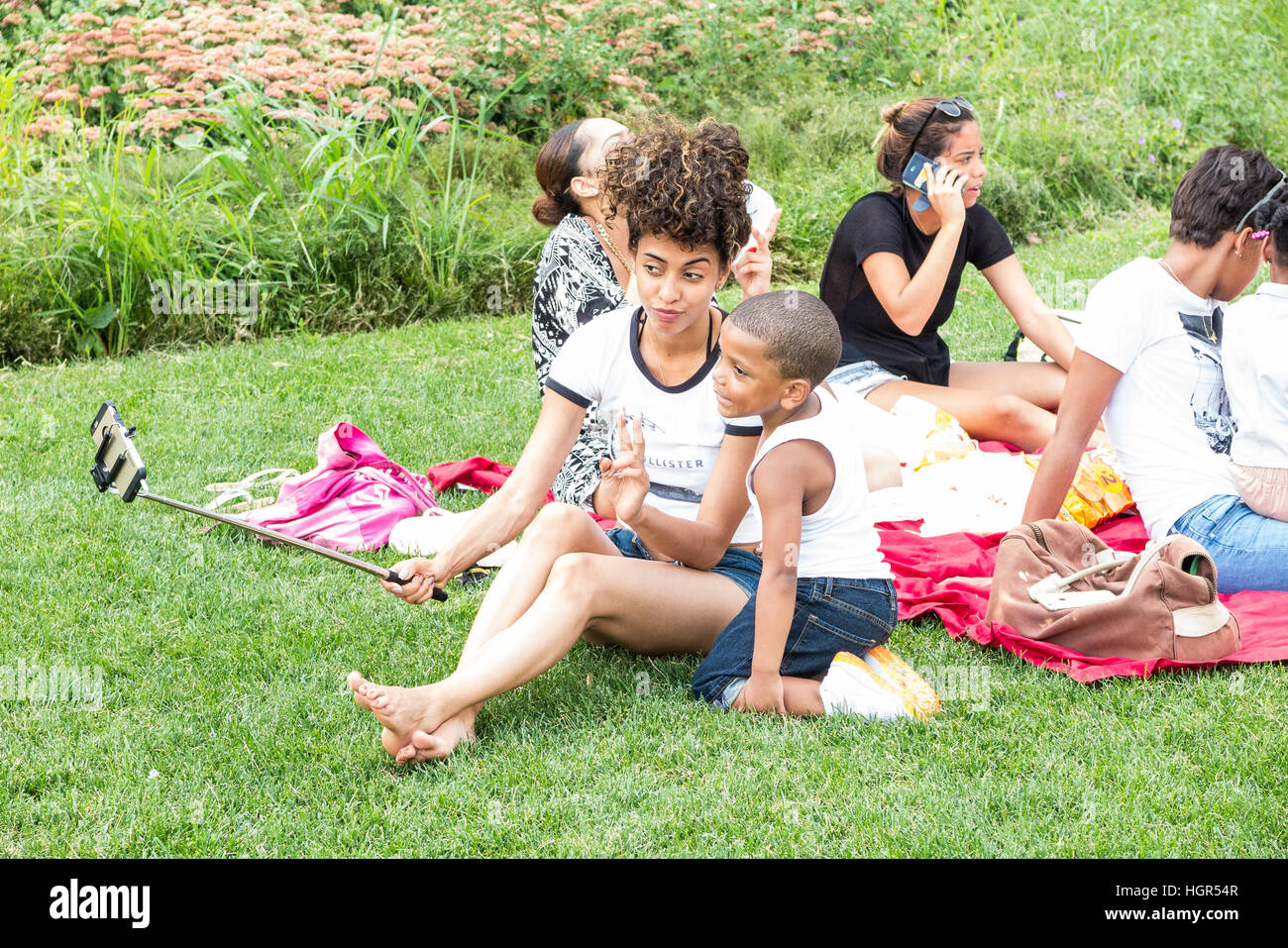 Young woman taking a photograph of herself/selfie and her friends/family while picnicking on the lawn in New York - Stock Image