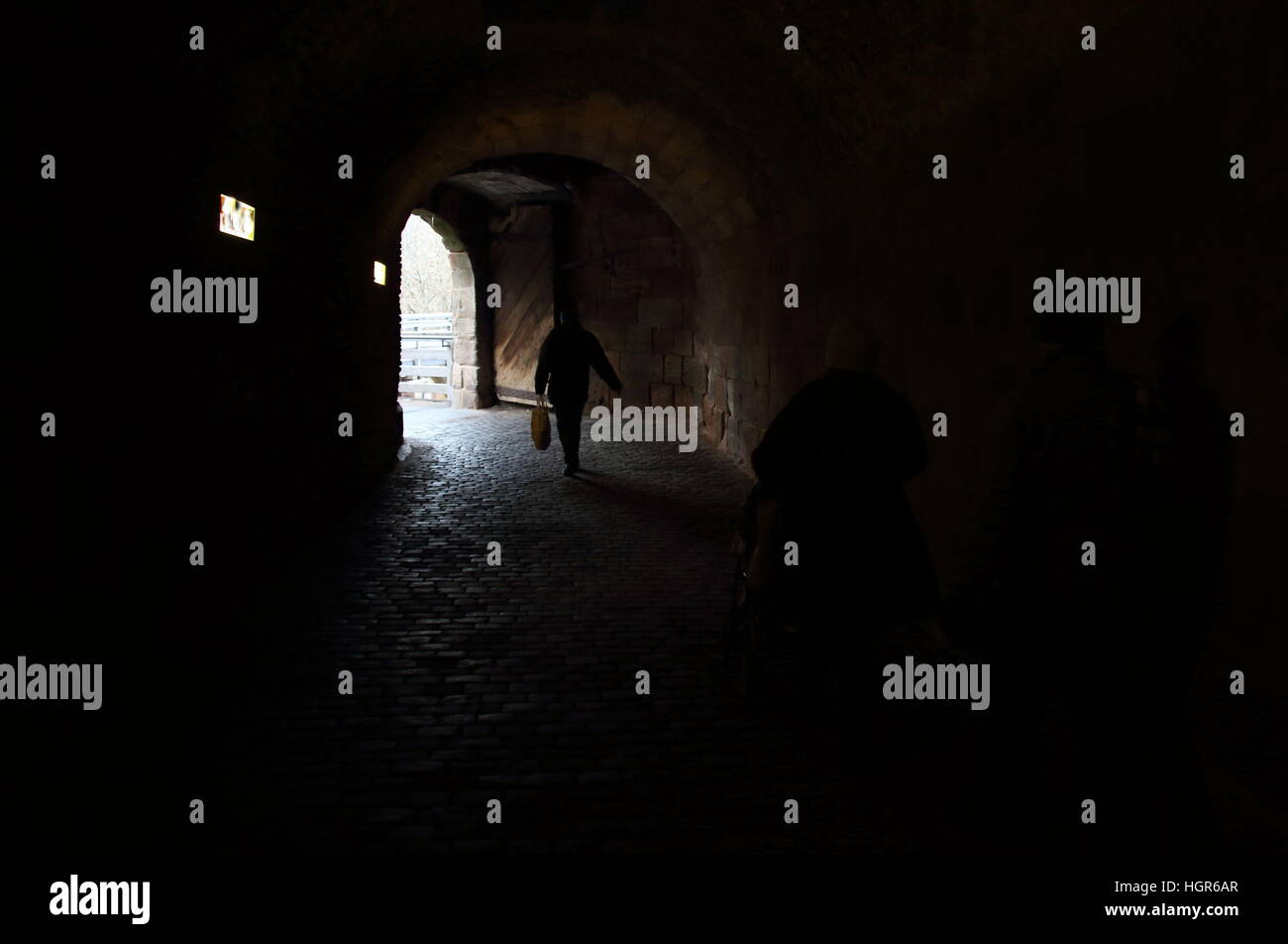 Shadowy figures in a dark tunnel - Stock Image
