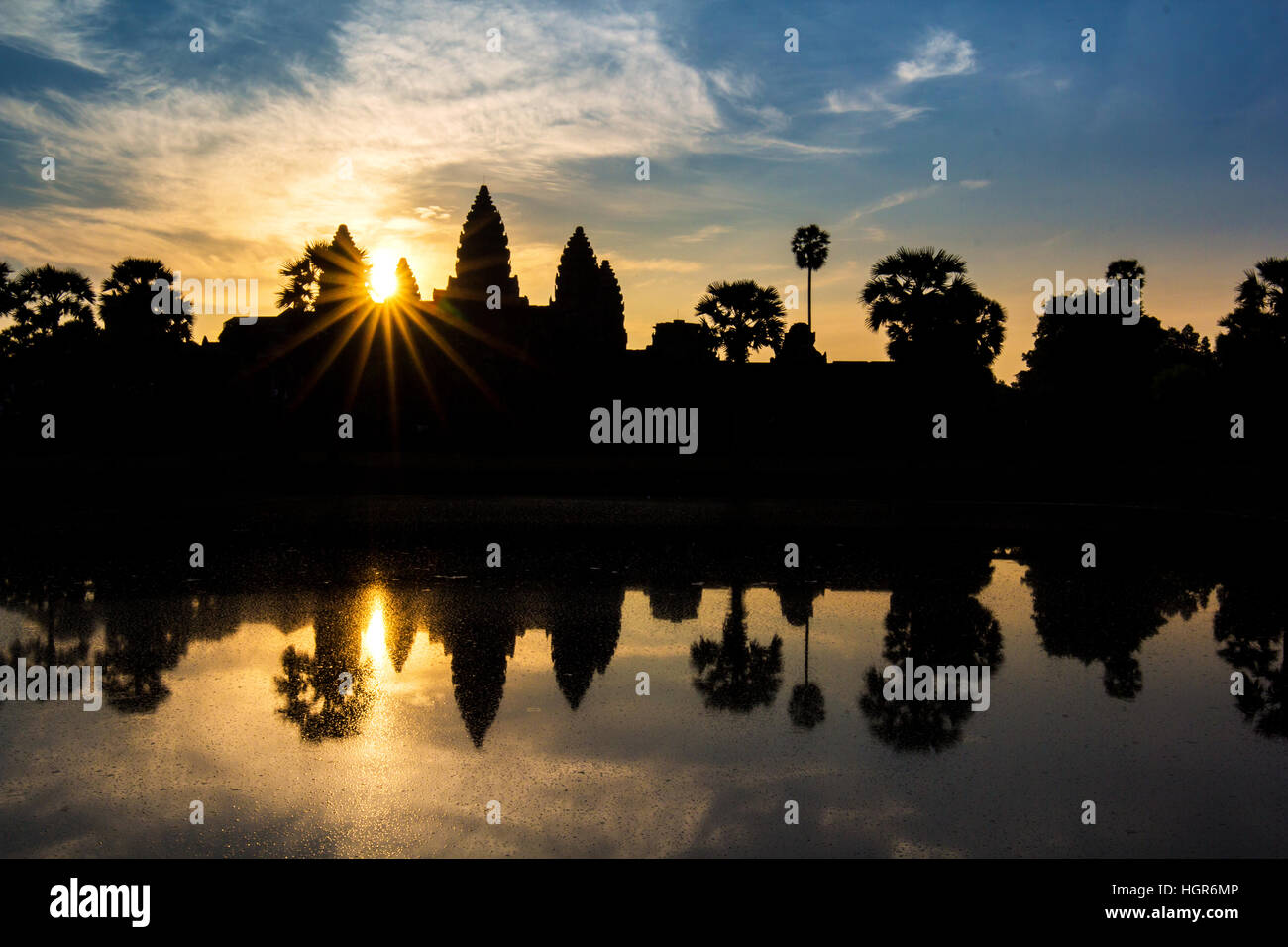 Angkor Wat temple at dramatic sunrise sunburst reflecting in water - Stock Image