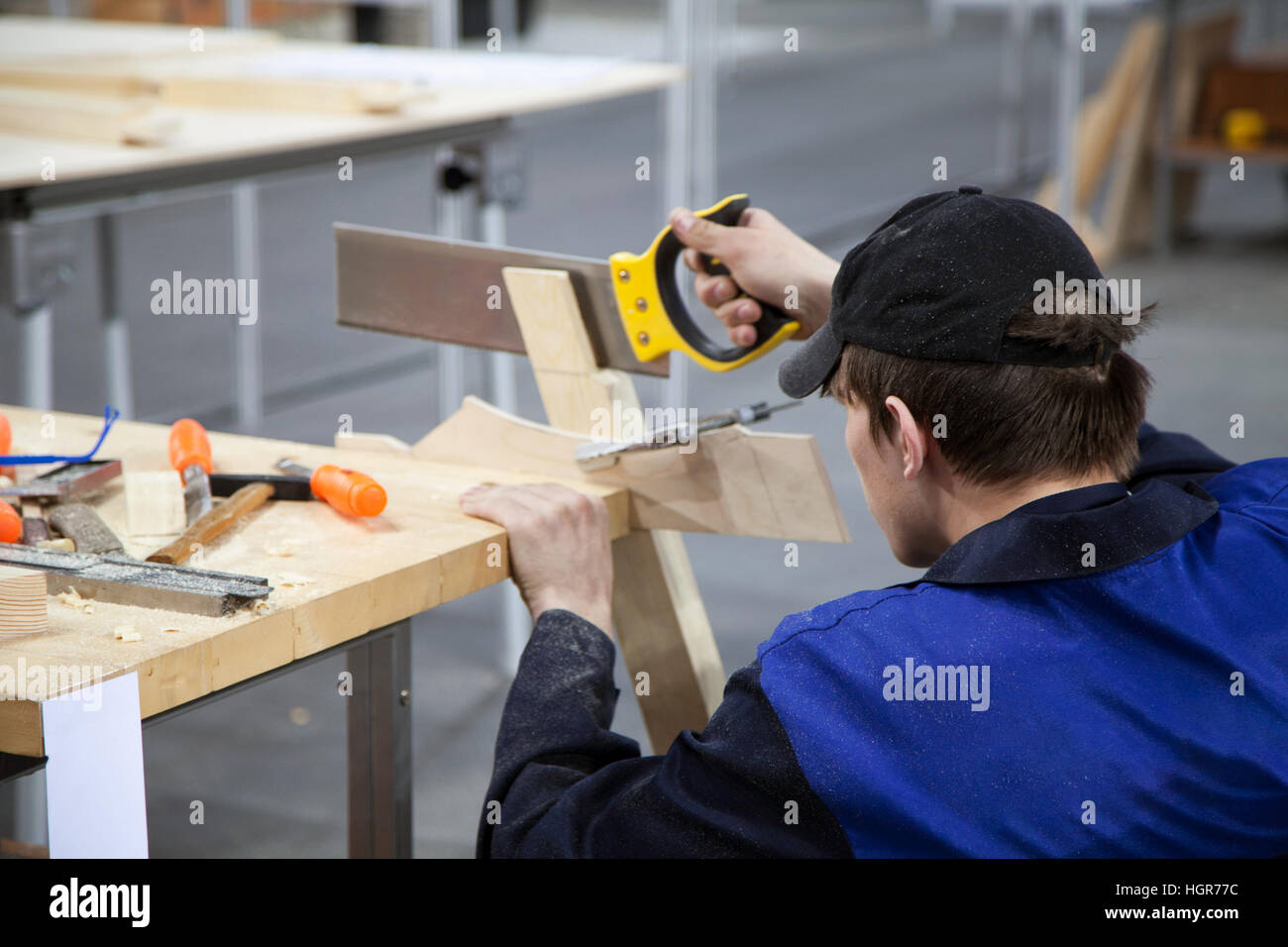 Carpenter in a blue uniform working with a saw and wood at the workshop. Young Caucasian man at the workbench with - Stock Image