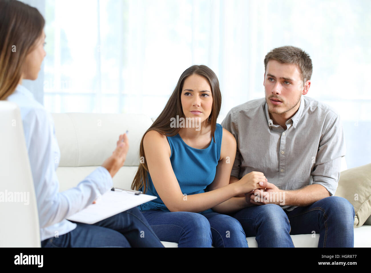 Worried couple listening to marriage counselor during a therapy sitting on a sofa at home - Stock Image