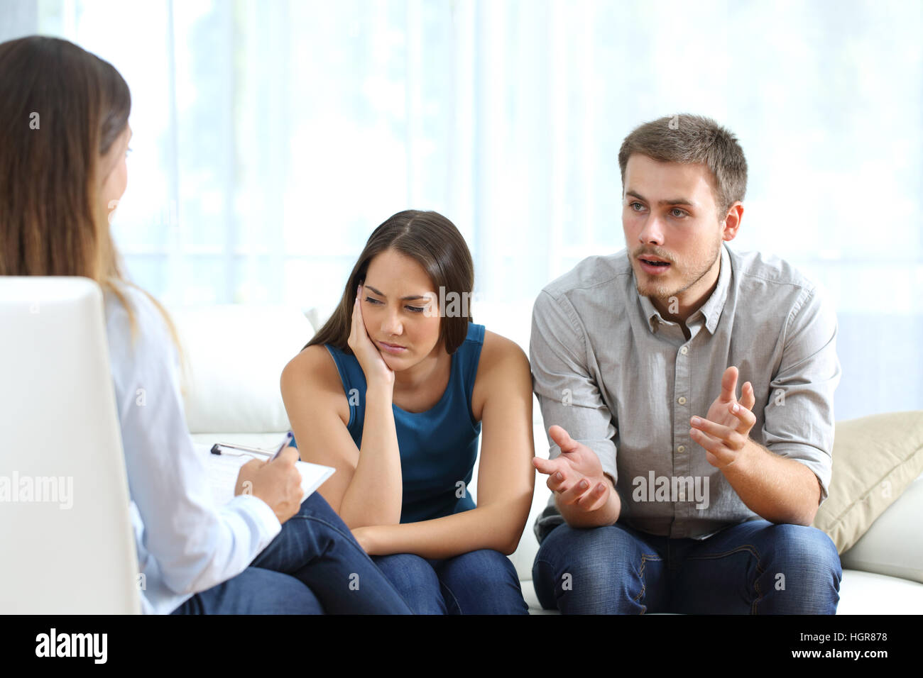 Angry husband and sad wife talking with a marriage counselor before breaking up sitting on a sofa at home - Stock Image