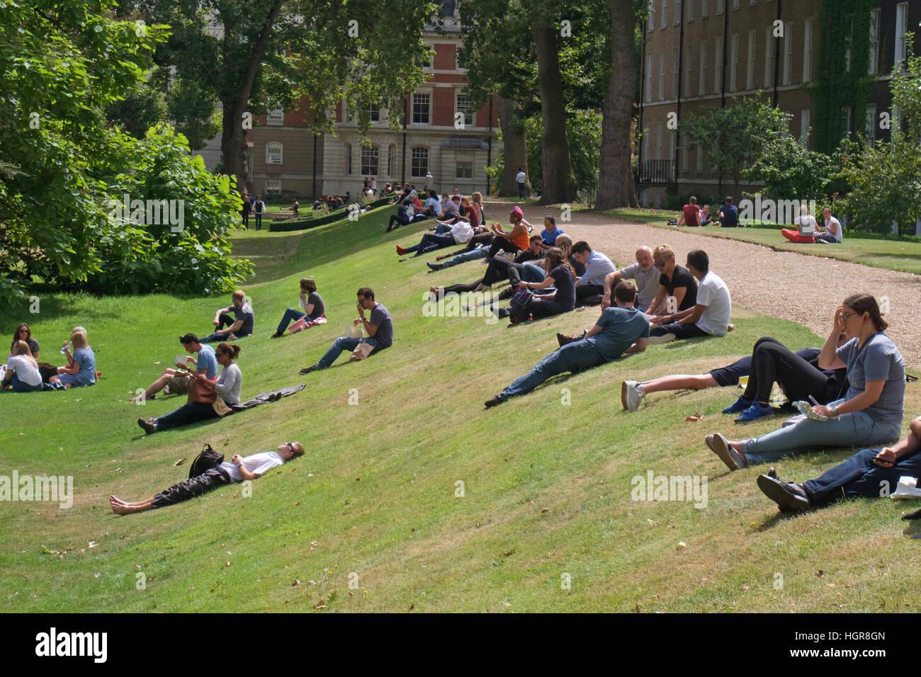 People enjoying the sunshine in Gray's Inn Gardens, London - Stock Image