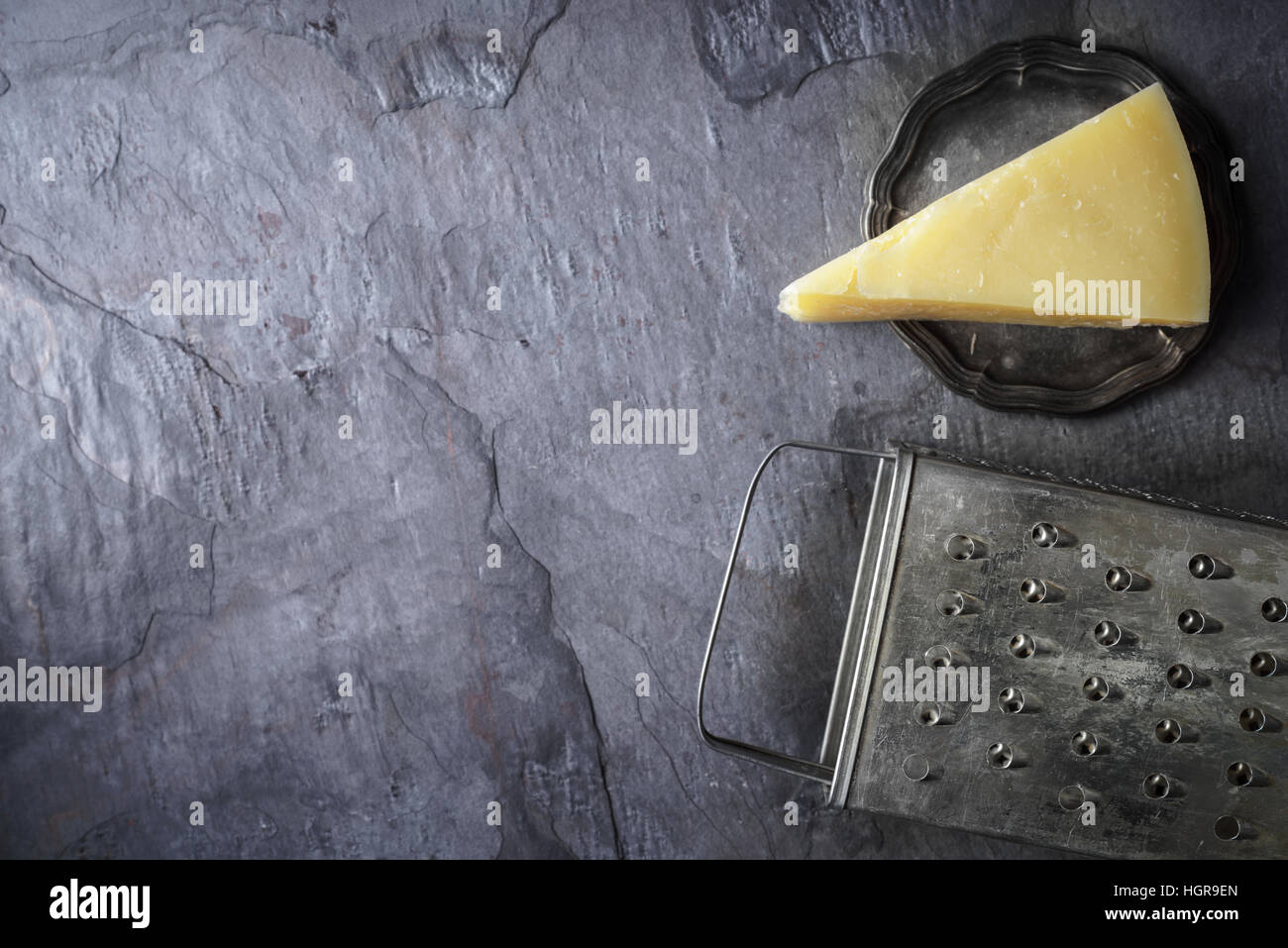 Cheese and grater on the stone background top view - Stock Image
