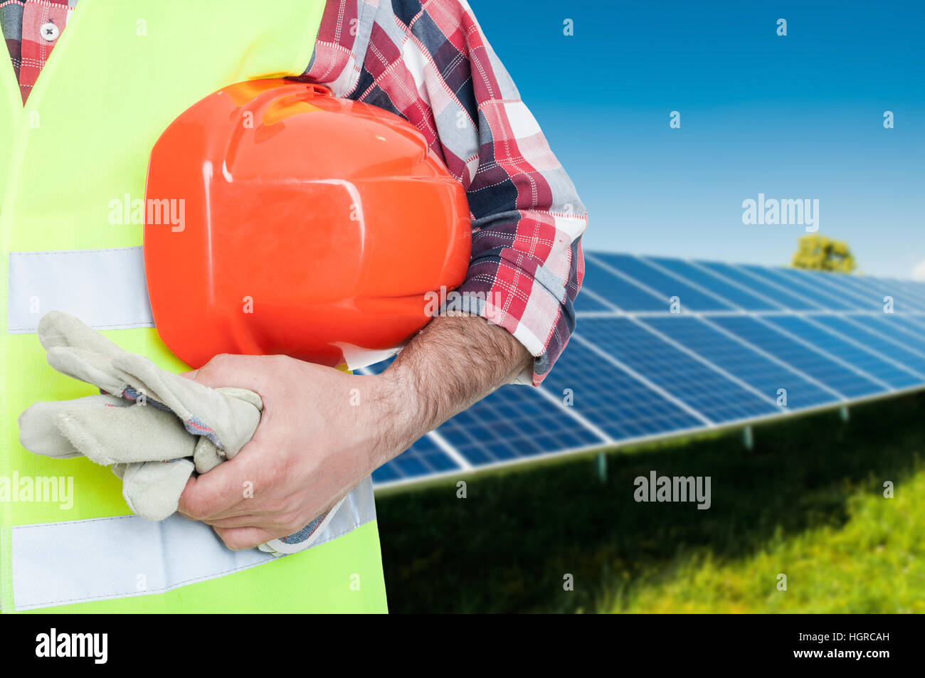 Male worker at photovoltaic panels holding safety uniform in close-up view with advertising area - Stock Image