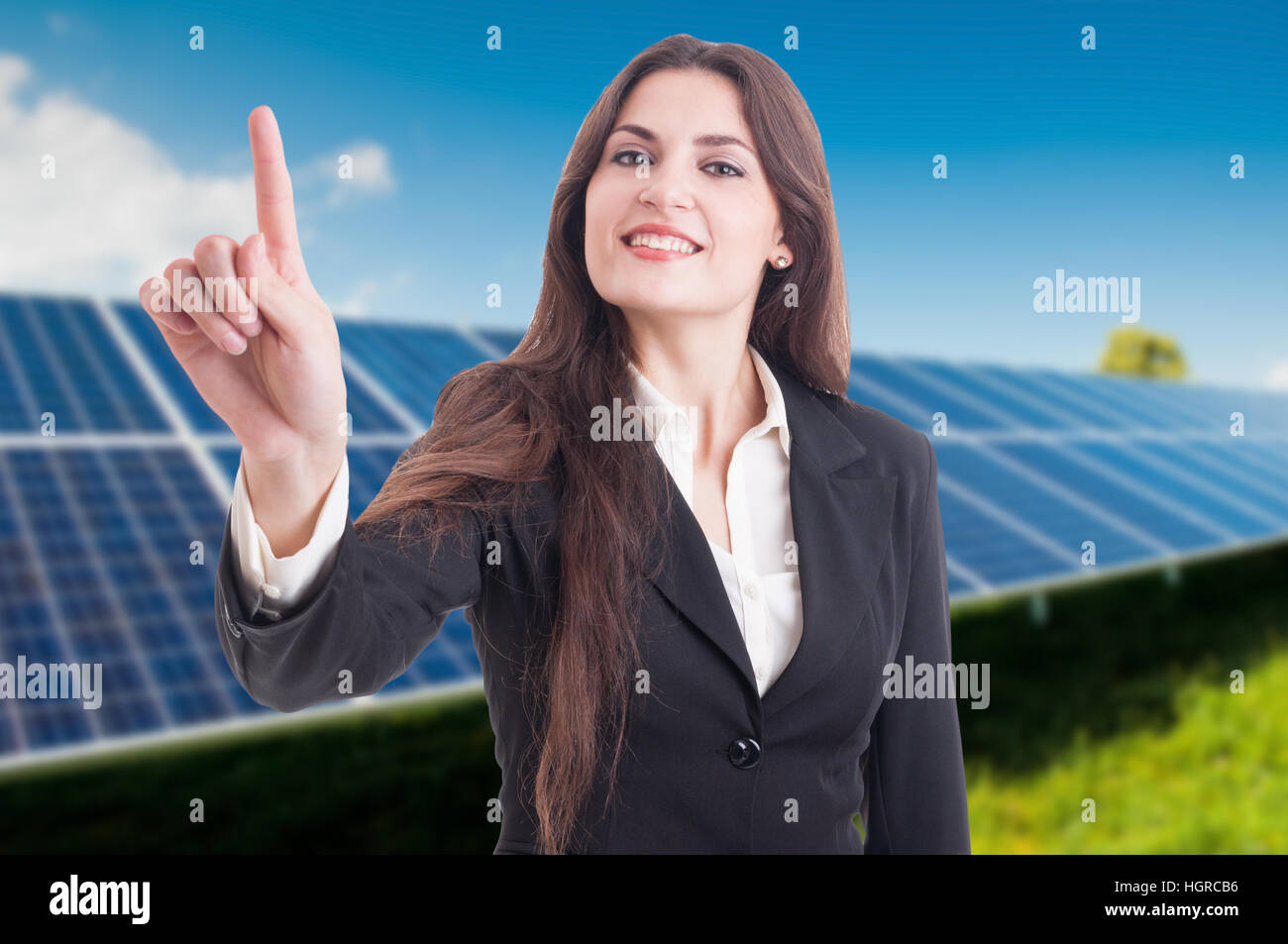 Beautiful business woman presing on invisible screen while using solar energy - Stock Image