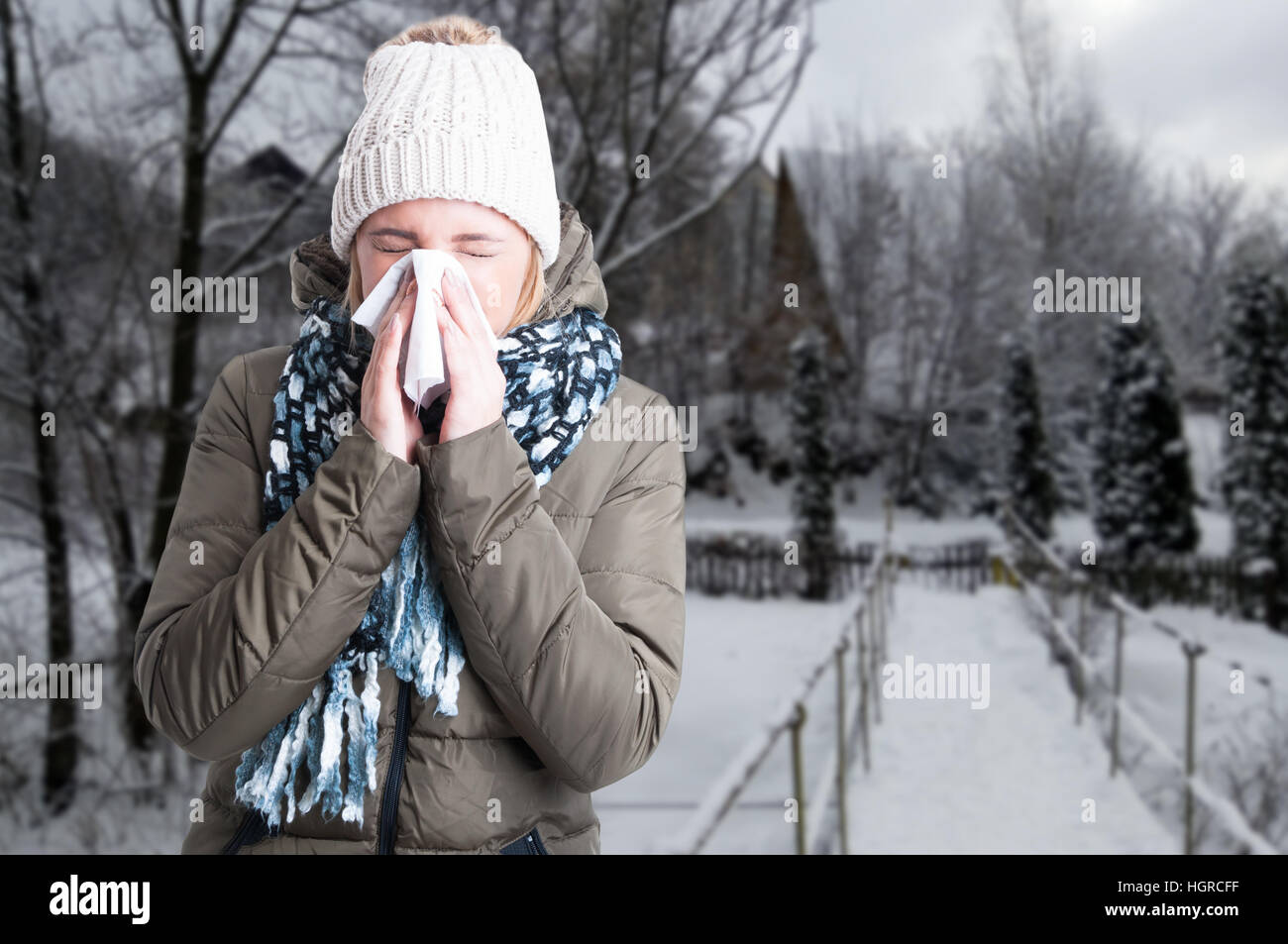 Winter illness concept with woman blowing into napkin outside in the snowy day with copy text space - Stock Image