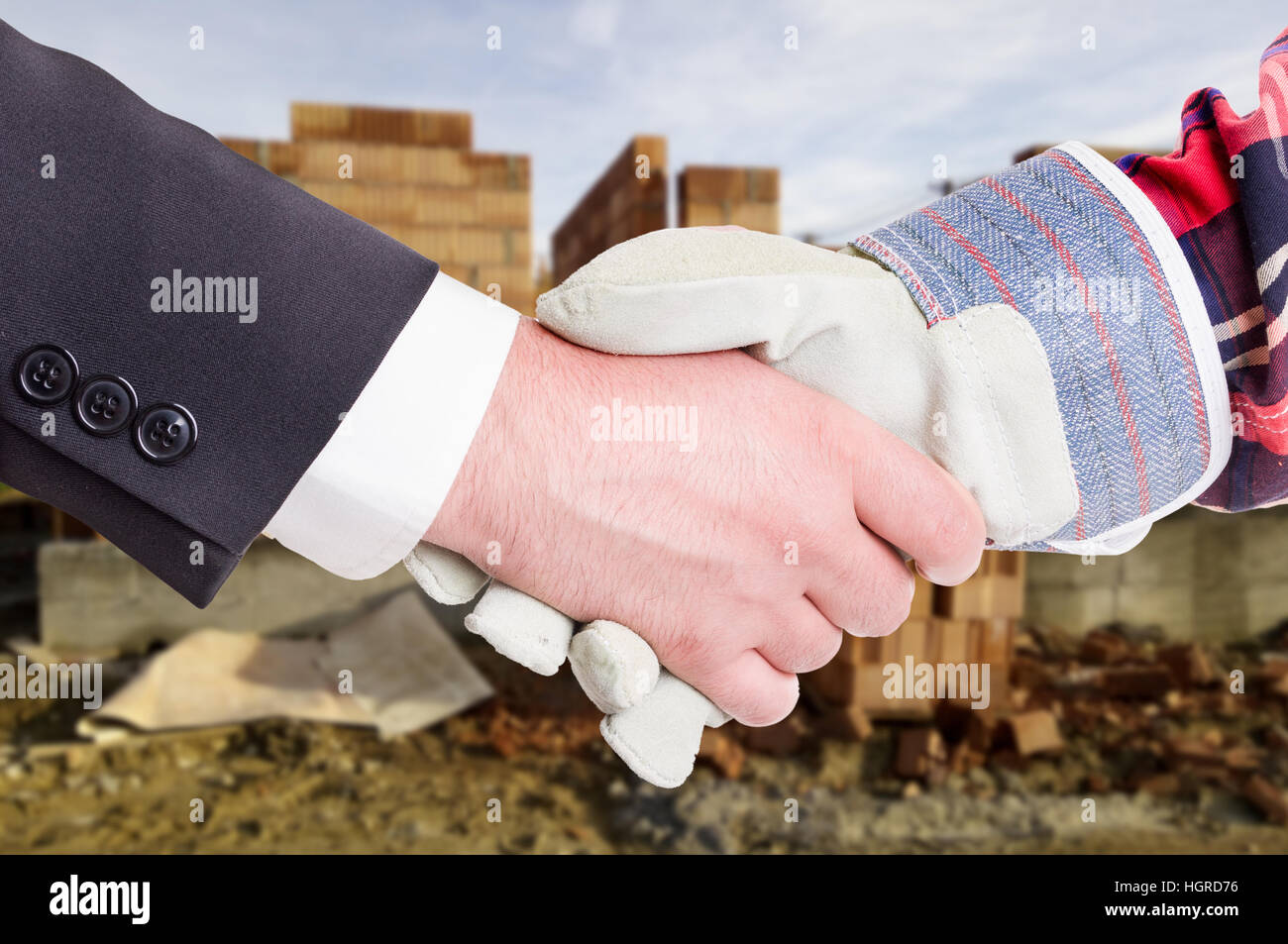Business handshake in closeup with constructor and businessman as successful construction partnership concept - Stock Image