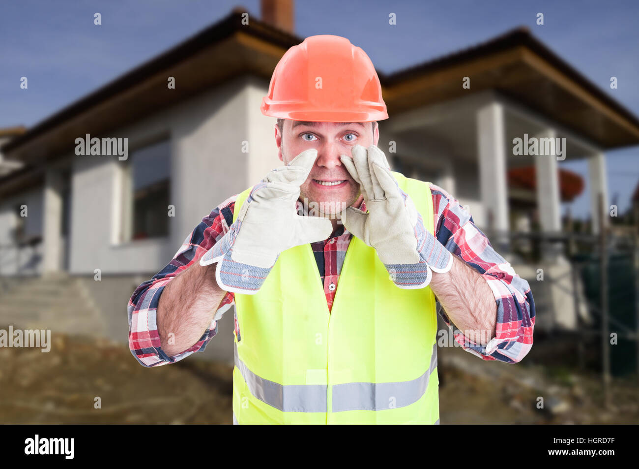 Constructor on construction site with protection equipment screaming or announcing something - Stock Image