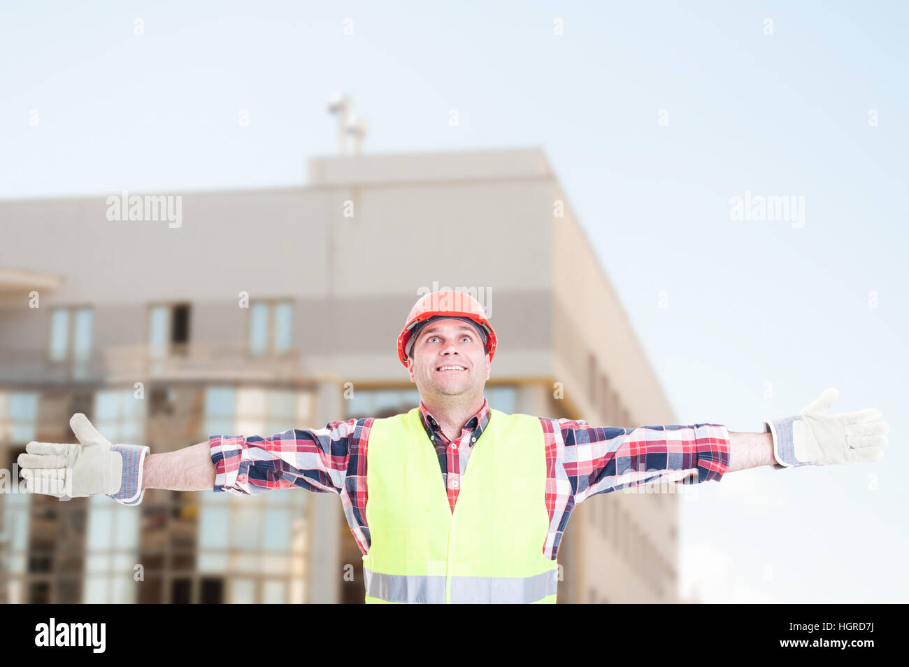 Cheerful constructor standing outside and celebrating victory with copy text area - Stock Image