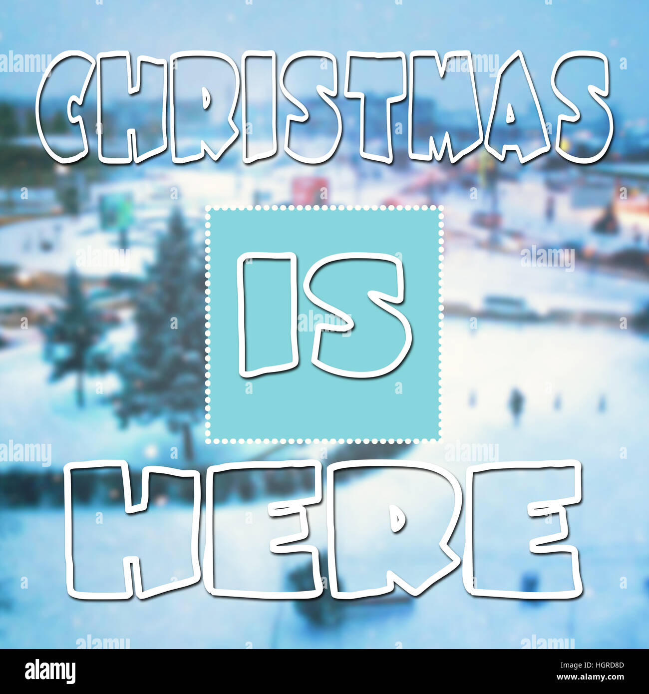 Christmas is here typographic quote on blurred wallpaper with snow - Stock Image