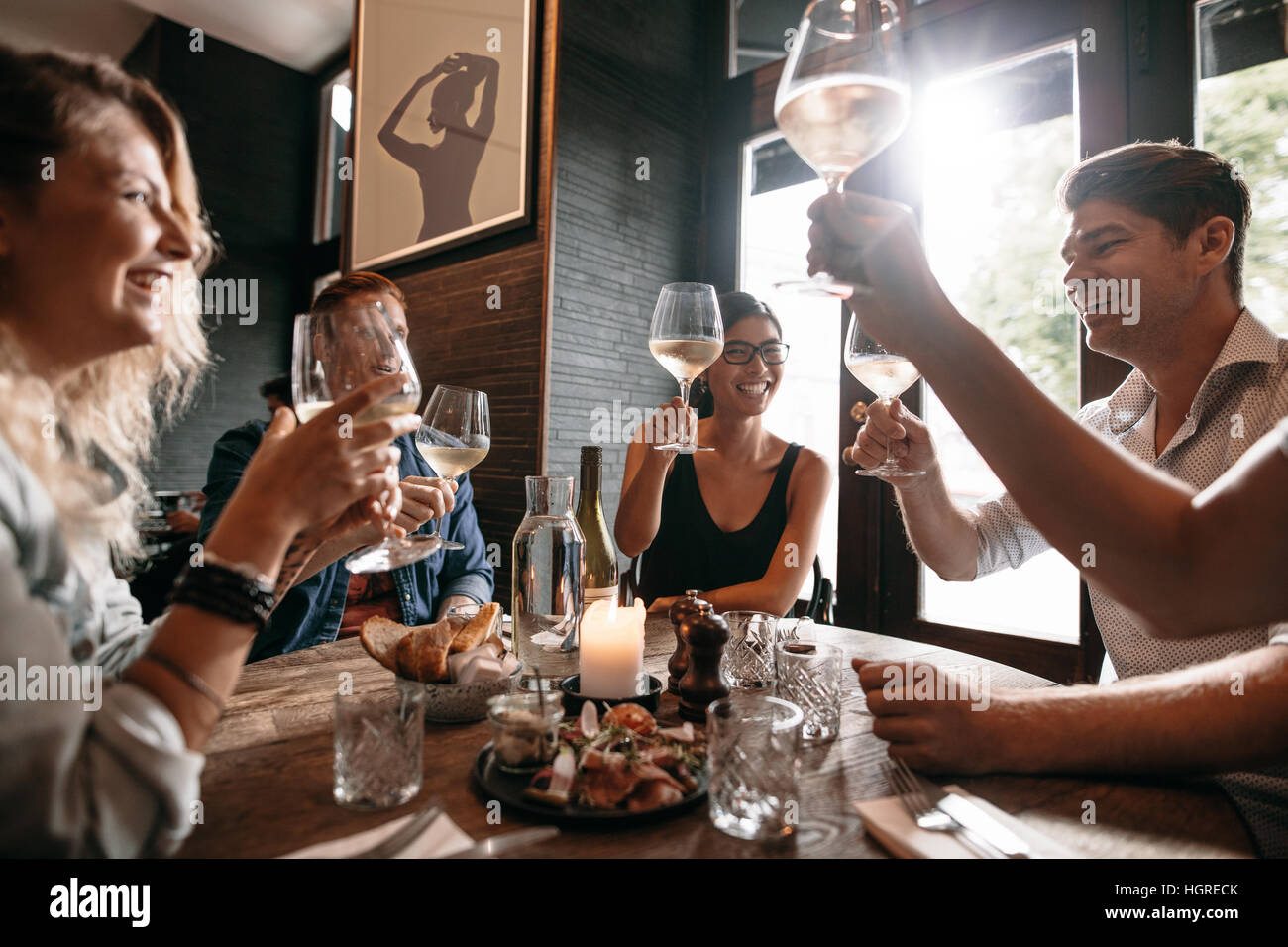 Group of friends making a toast at restaurant. Young people friends sitting at a table, toasting with wine and enjoying - Stock Image