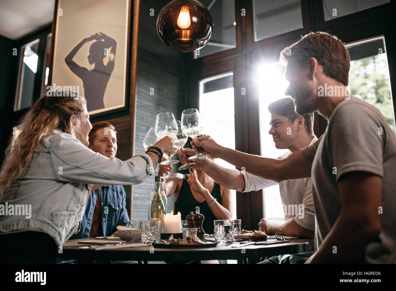 Young man and woman sitting at table and toasting drinks at restaurant. Group of friends toasting wine at cafe. - Stock Image