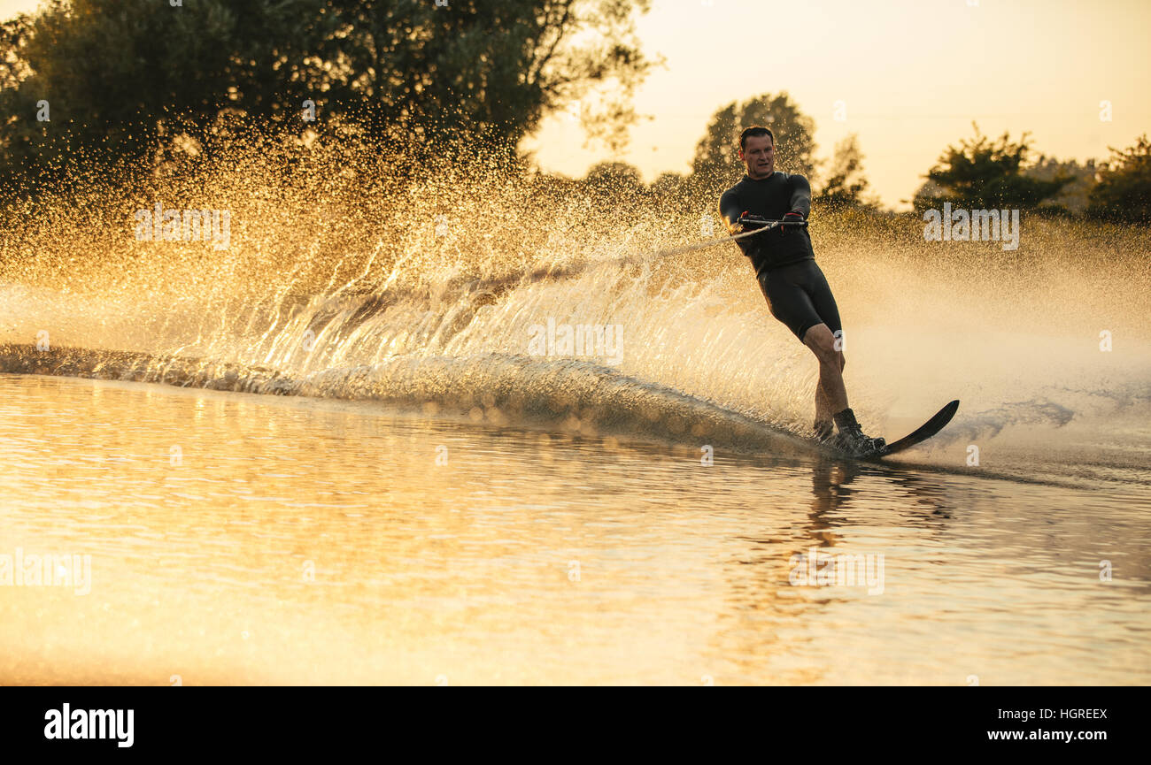 Man riding wakeboard in a lake. Water skier in action on the lake - Stock Image