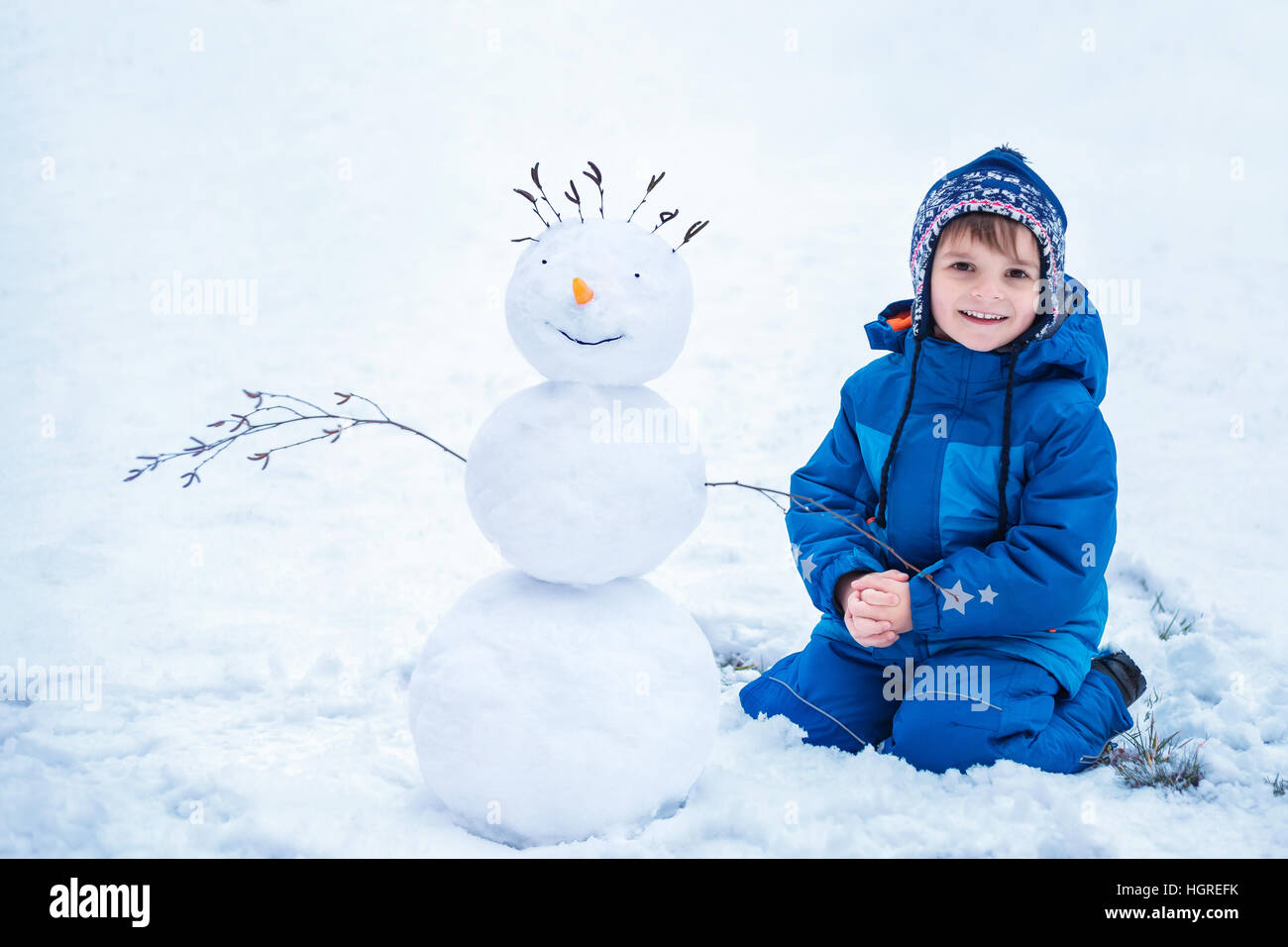 little boy sitting near the smiling snowman - Stock Image