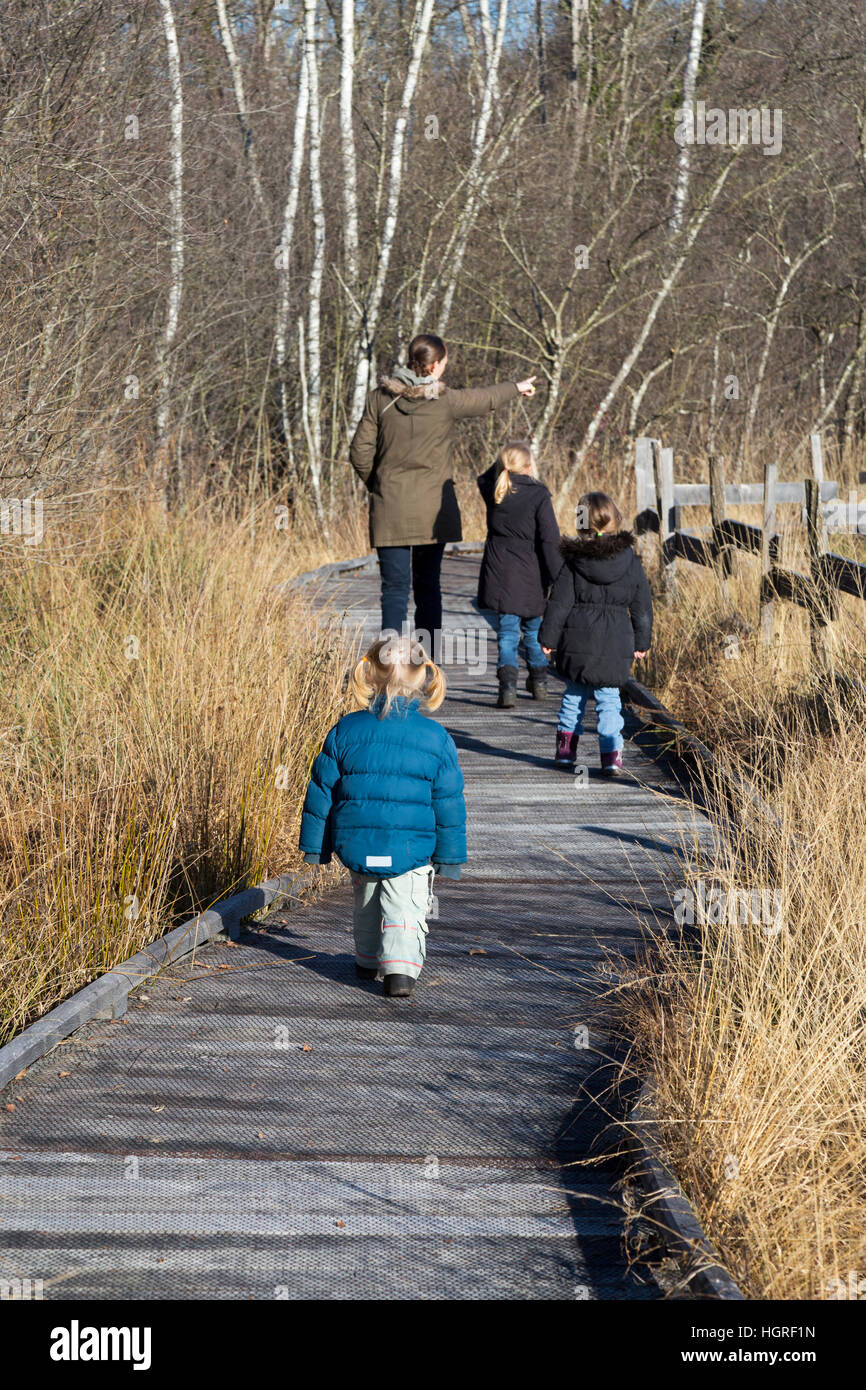 Mother & 3 children three kids daughters on walkway pathway foot path footpath Marais de Lavours National Nature - Stock Image