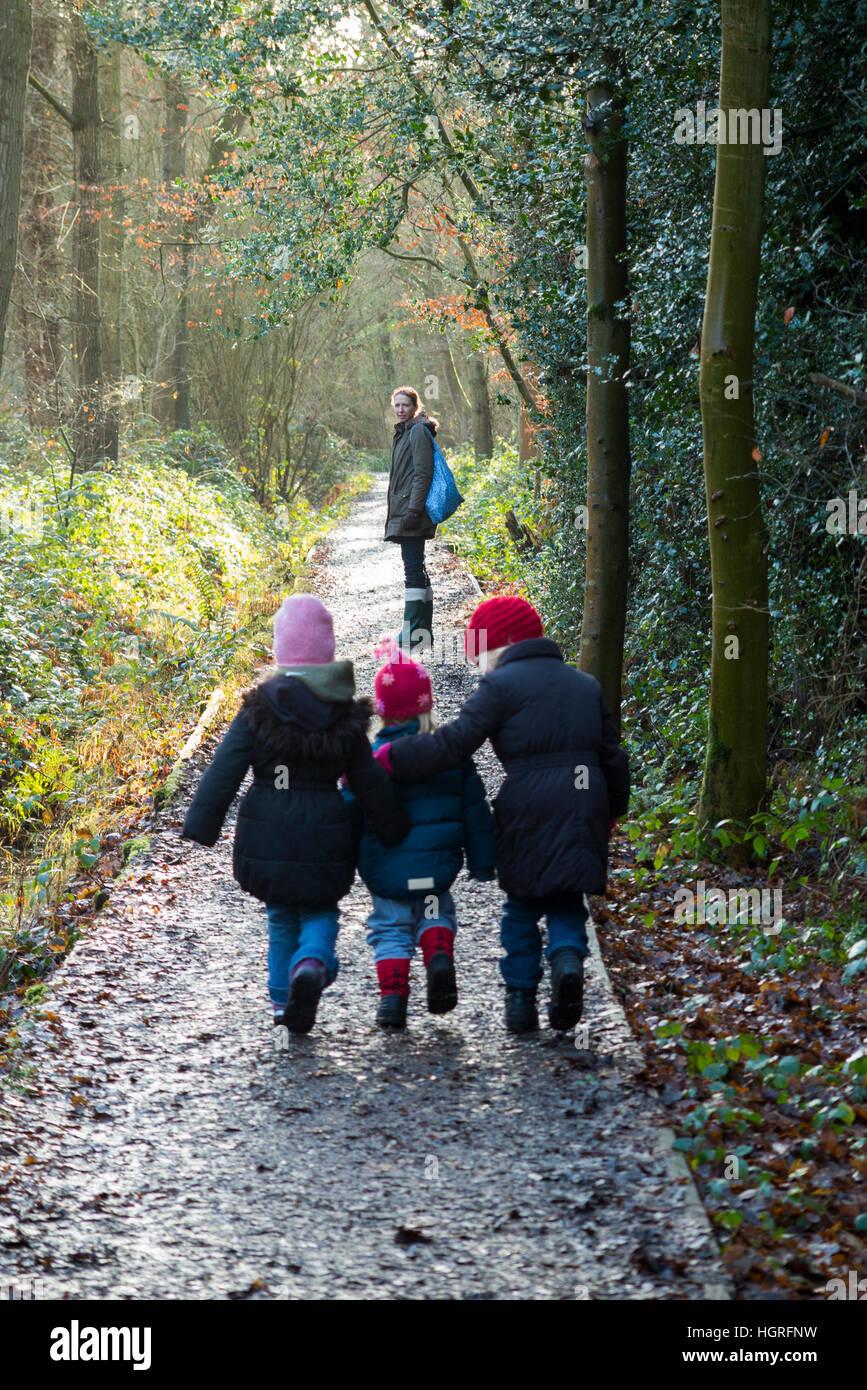 Mother & 3 children three kids daughters walking / walk along muddy path / in mud on walkway pathway foot path footpath Stock Photo