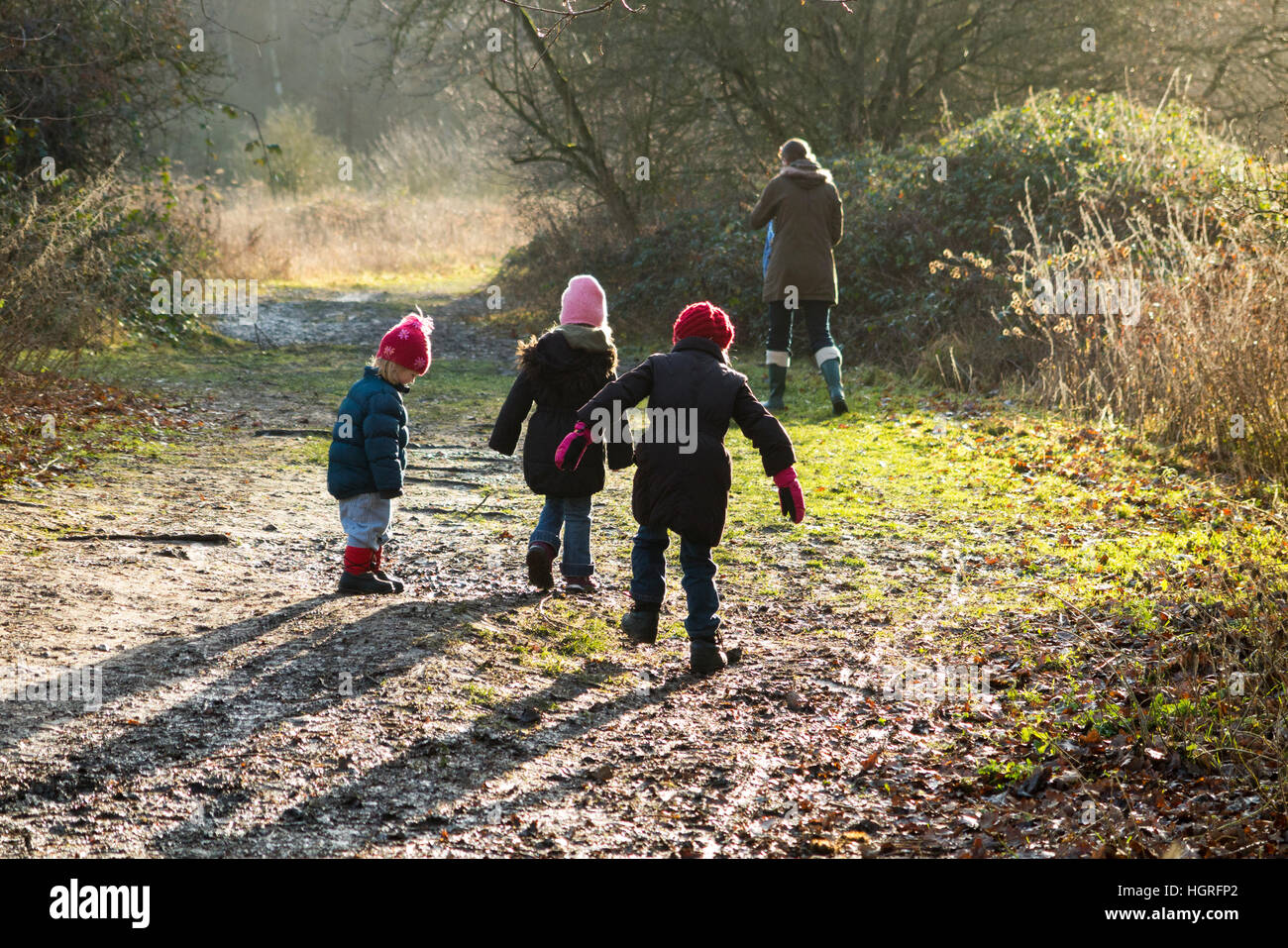 Mother & 3 children three kids daughters walking / walk along muddy path / in mud on walkway pathway foot path - Stock Image