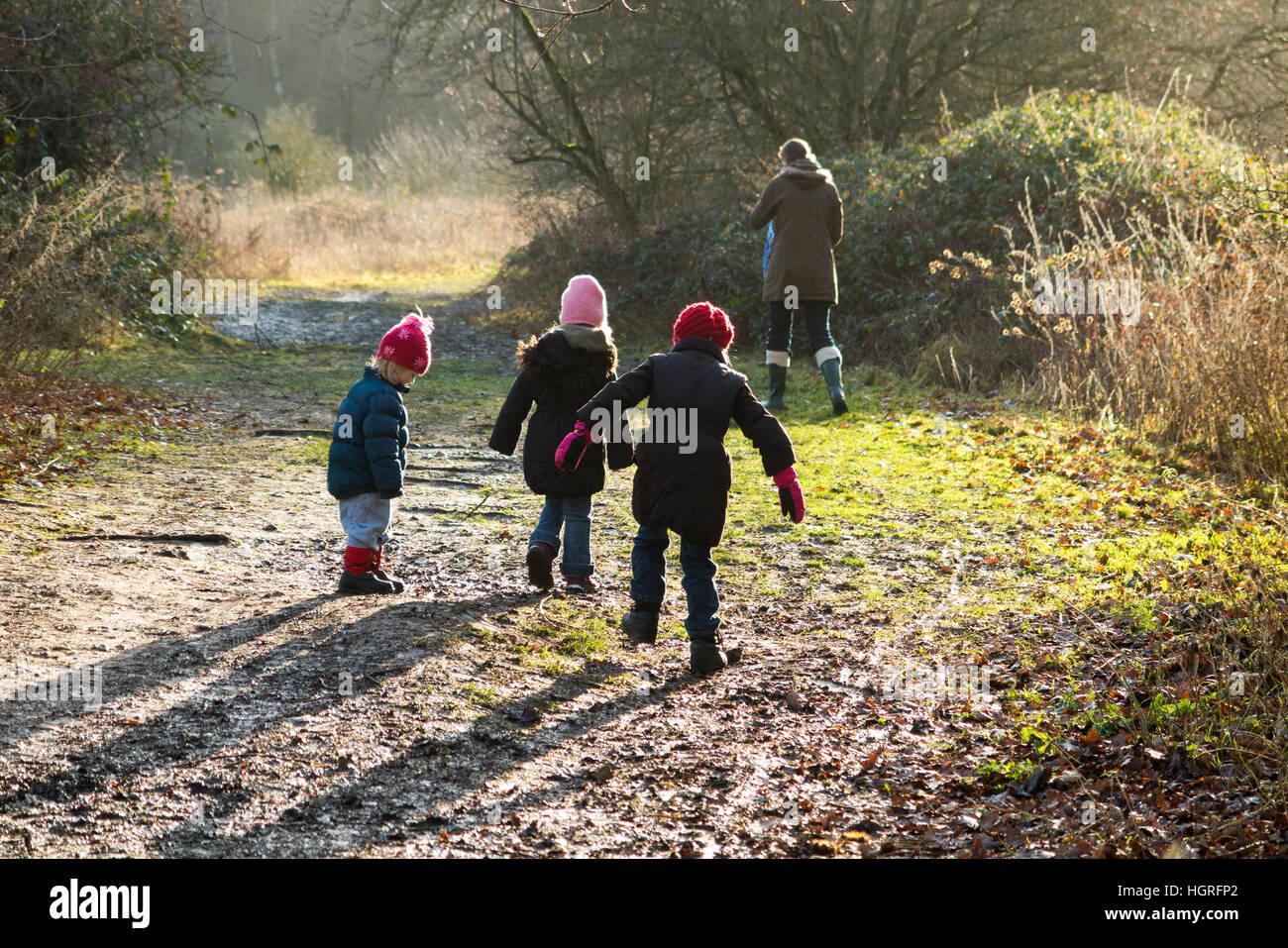 Mother & 3 children three kids daughters walking / walk along muddy path / in mud on walkway pathway foot path - Stock Image