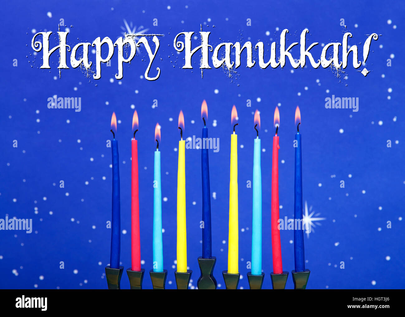 a nine-branched menorah (also called a Chanukiah or Hanukiah) burning candles to celebrate Hanukkah against a blue - Stock Image