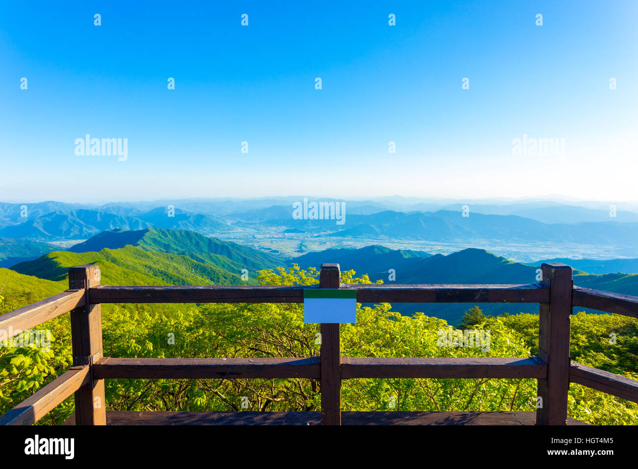 Wooden viewpoint deck offering clear view of valley below from atop Jirisan Mountain in South Korea. Horizontal - Stock Image