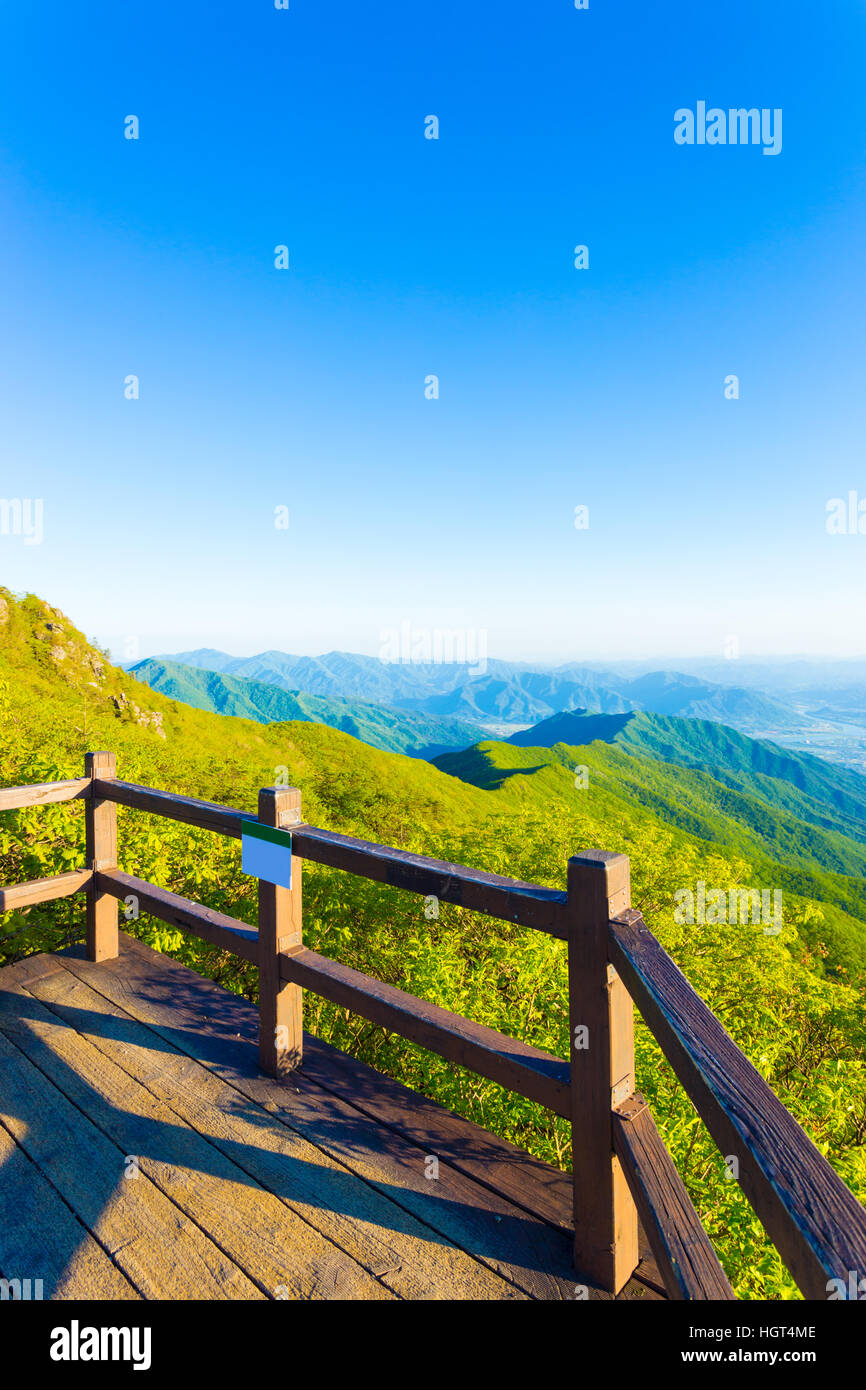 Wooden viewpoint deck offering clear view of valley below from atop Jirisan Mountain in South Korea. Vertical - Stock Image