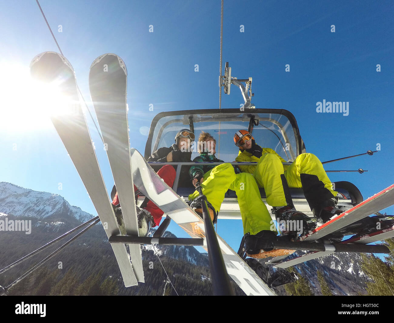 Three teenagers on chairlift with skis and snowboard, taking selfie, Spitzingsee ski resort, Bavaria, Germany - Stock Image