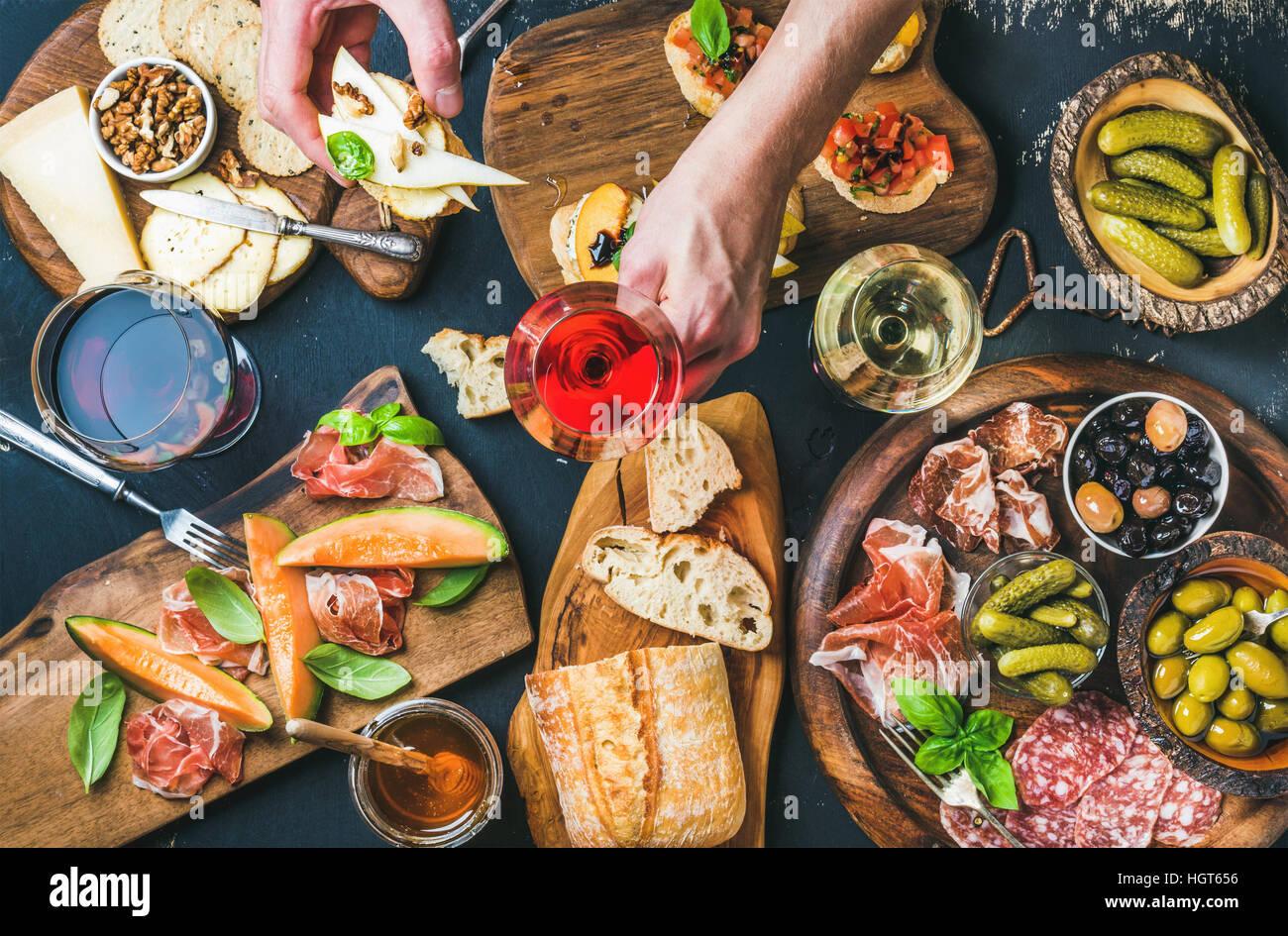 Italian wine snacks set, man's hand holding glass of rose - Stock Image