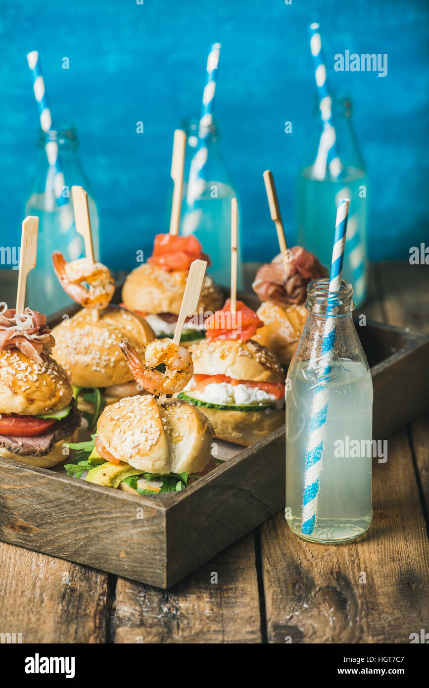 Different homemade burgers with sticks in wooden tray and lemonade - Stock Image