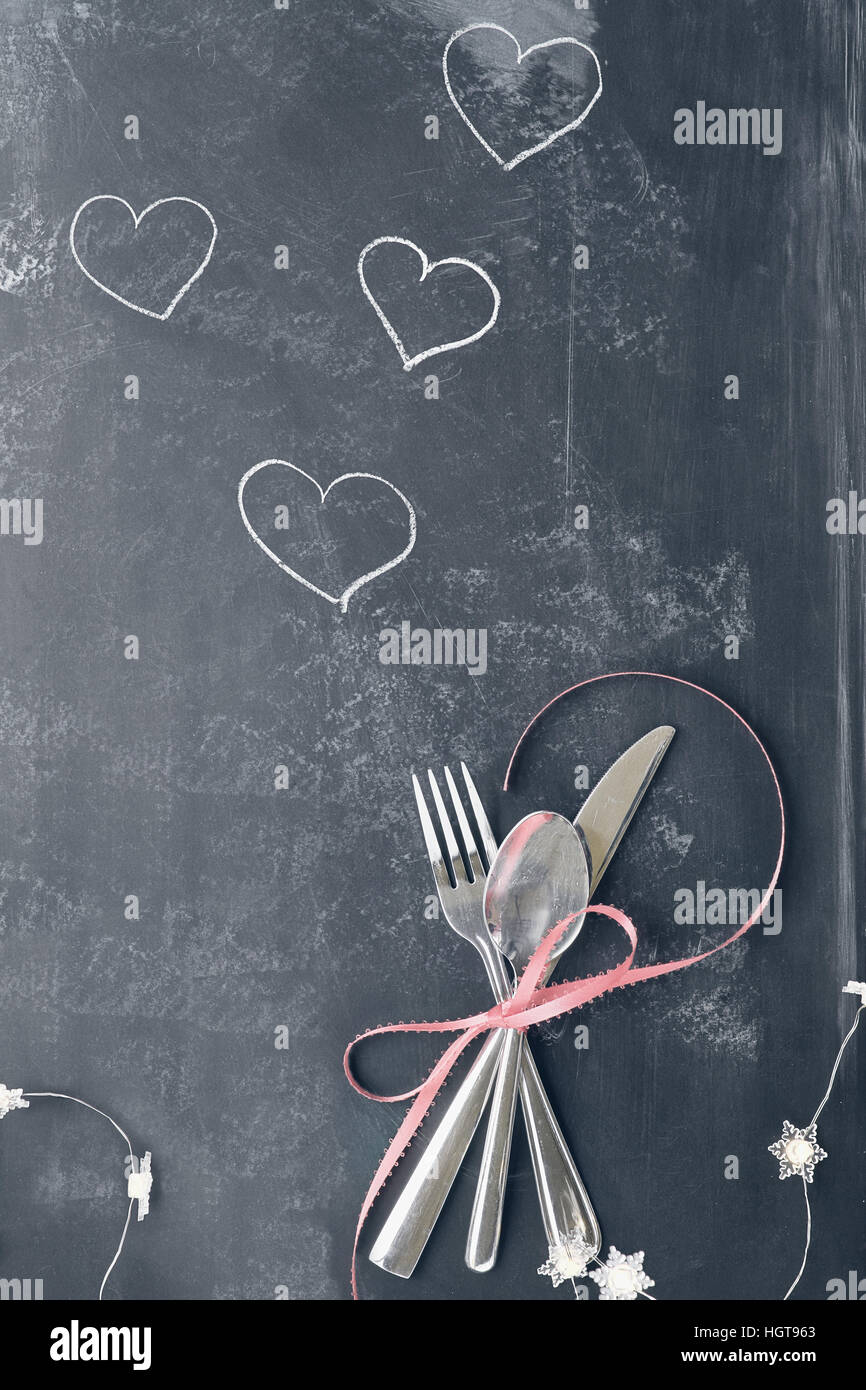 Top view of Valentines day dinner table setting with cutlery over a rustic blackboard background with fairy lights and Instagram type faded filter. & Top view of Valentines day dinner table setting with cutlery over a ...