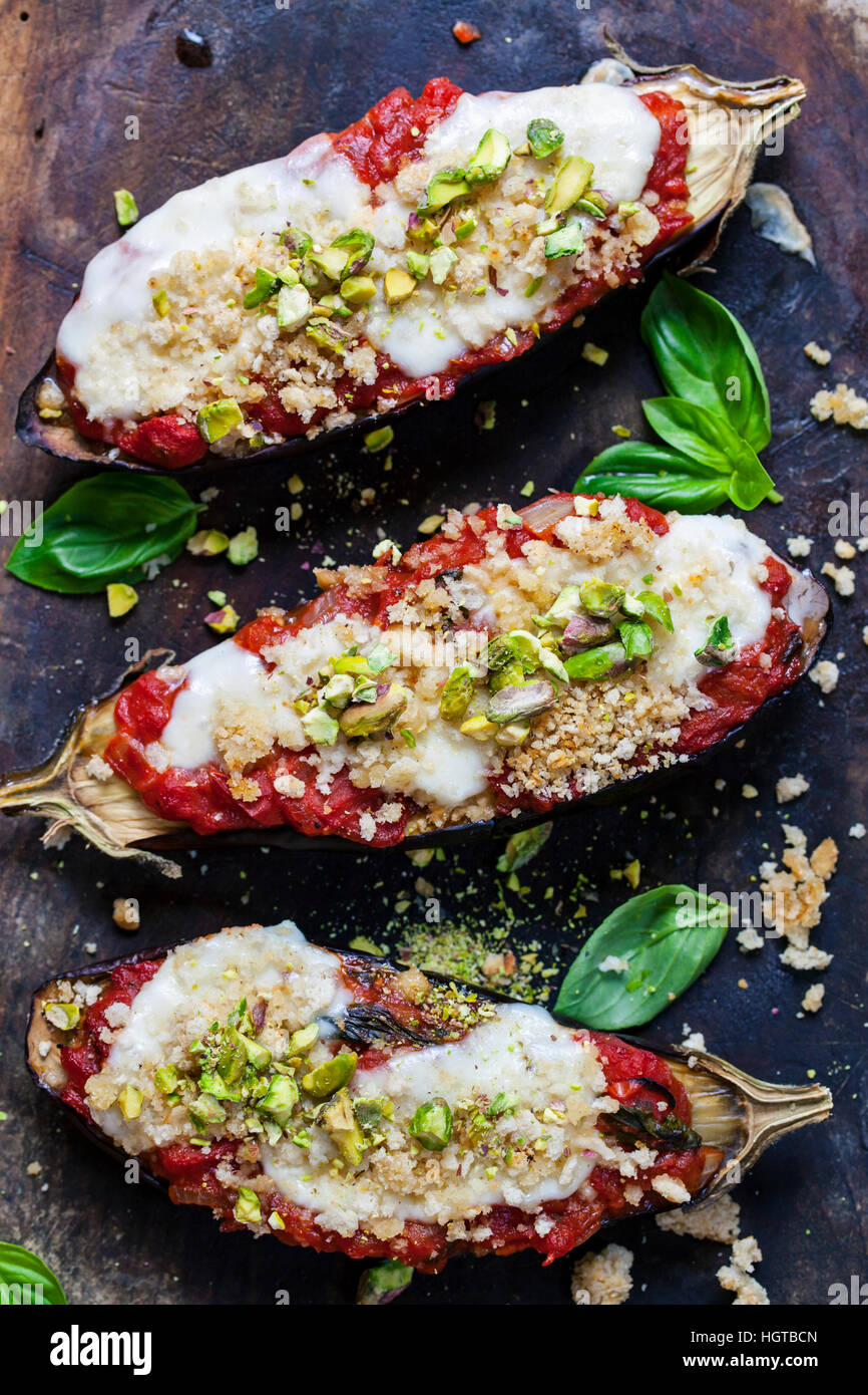 Roast aubergines with tomatoes mozzarella and pistachio nuts - Stock Image