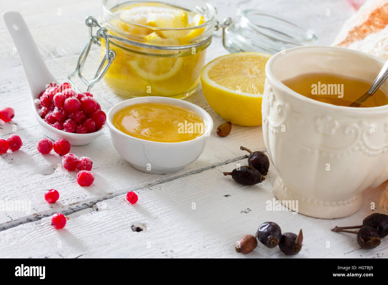 Treatment of seasonal colds - treatment in folk medicine, dietary sources of vitamin on a white table: lemon, honey, - Stock Image