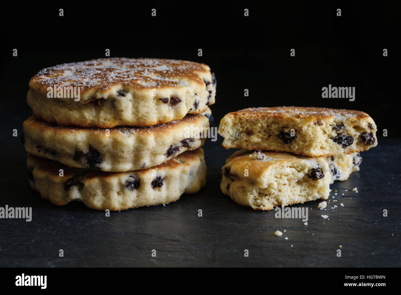 Welsh cakes a traditional griddle cake made with flour and dried fruit on a slate background - Stock Image