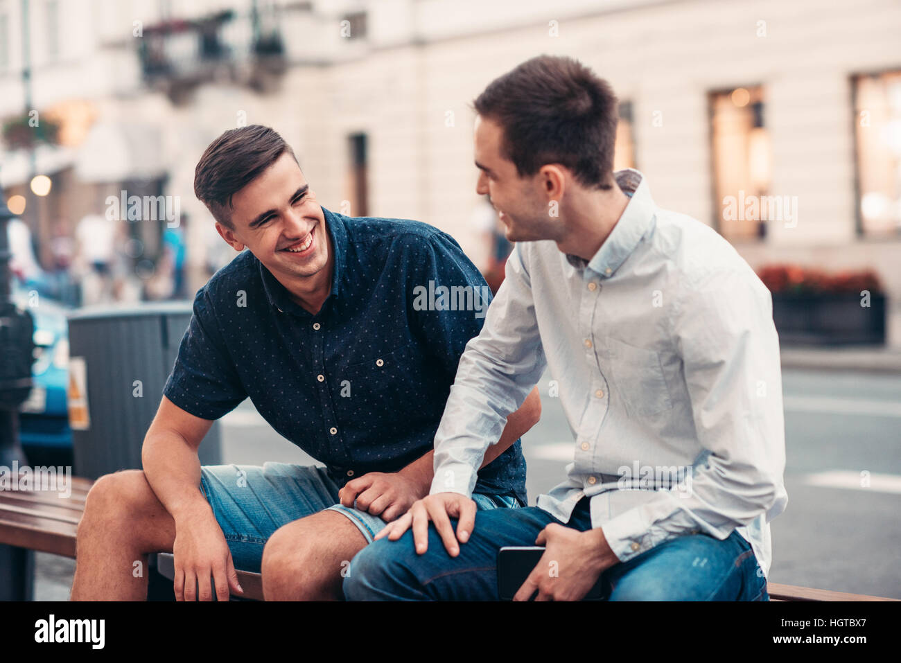 Friends talking together on a bench in the city - Stock Image