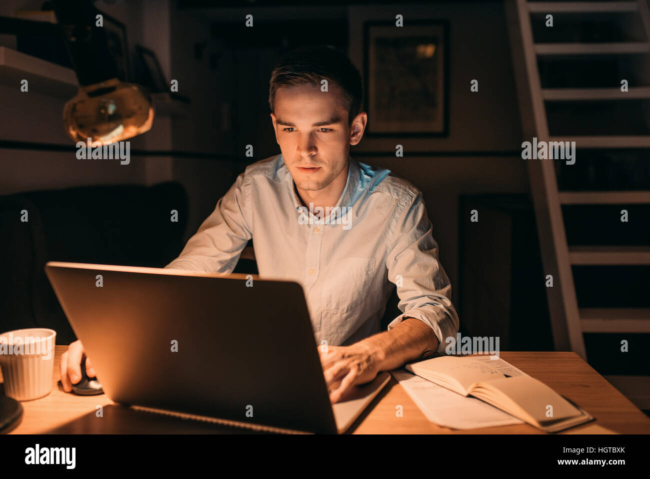 Young businessman working on a laptop late in the evening - Stock Image