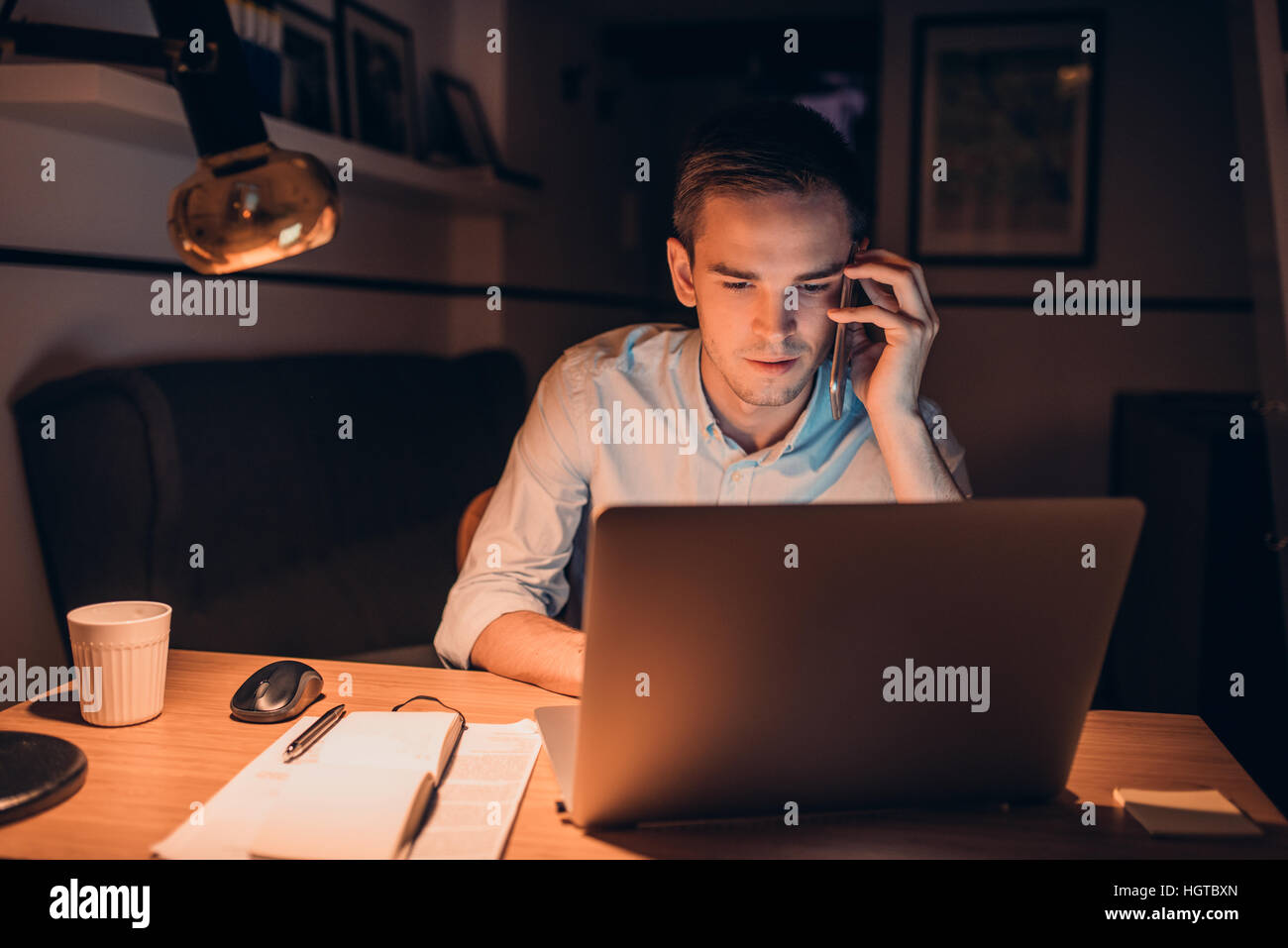 Young businessman hard at work late in the evening - Stock Image