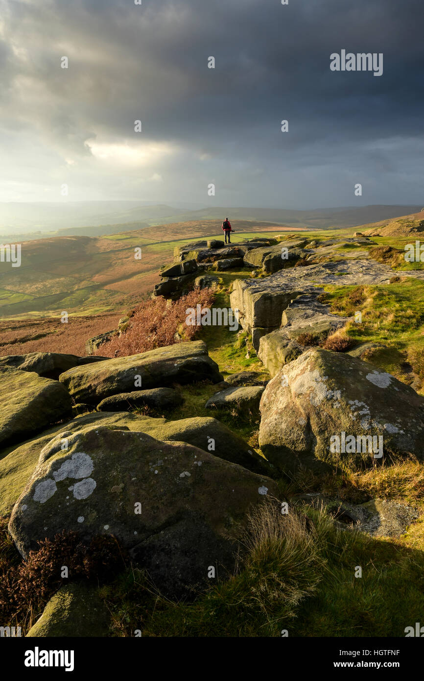 Person standing on rocks looking at sunset in the Peak District Derbyshire countryside - Stock Image