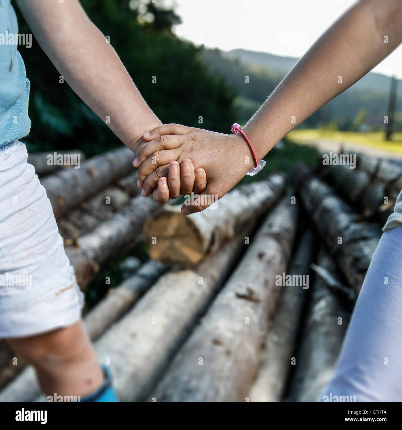 Friends holding hands, enjoying time together. Happy, carefree, outdoor countryside childhood, siblings love, companionship, - Stock Image