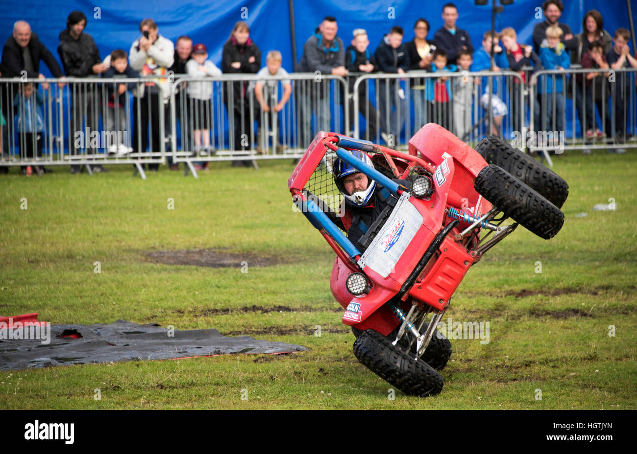Car driver performing daring stunt with 2 wheels off the ground. - Stock Image