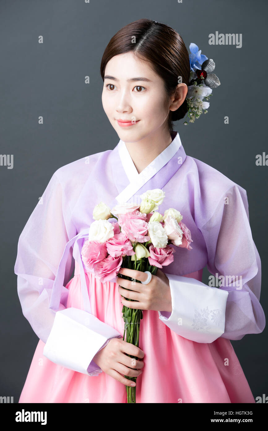 Young Woman In Traditional Korean Clothes Holding Flowers Stock