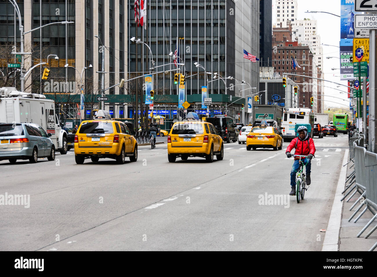 Cyclist riding against the flow of traffic on 6th Avenue in New York Stock Photo
