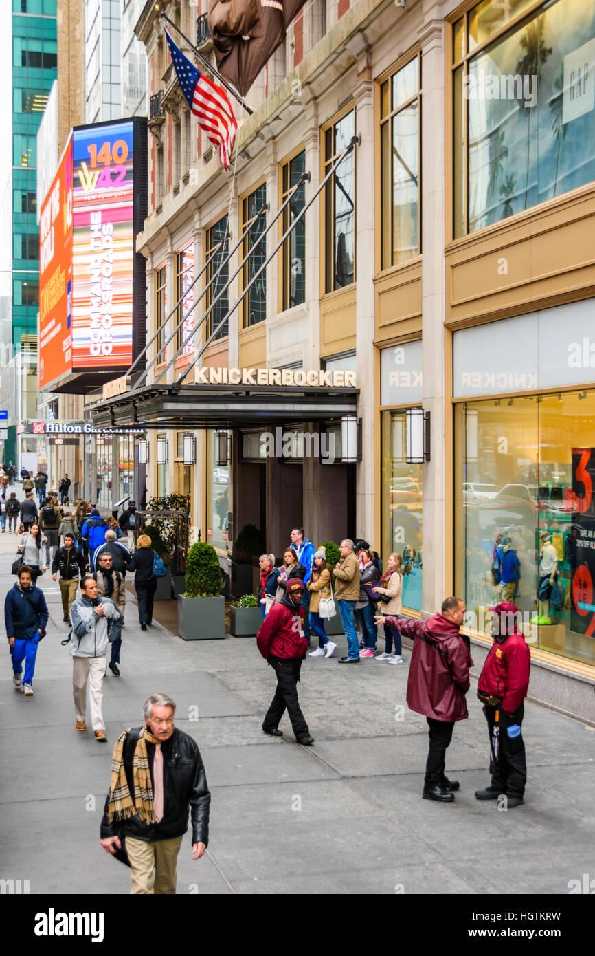 People walking along the sidewalk outside the Knickerbocker Hotel in New York Stock Photo