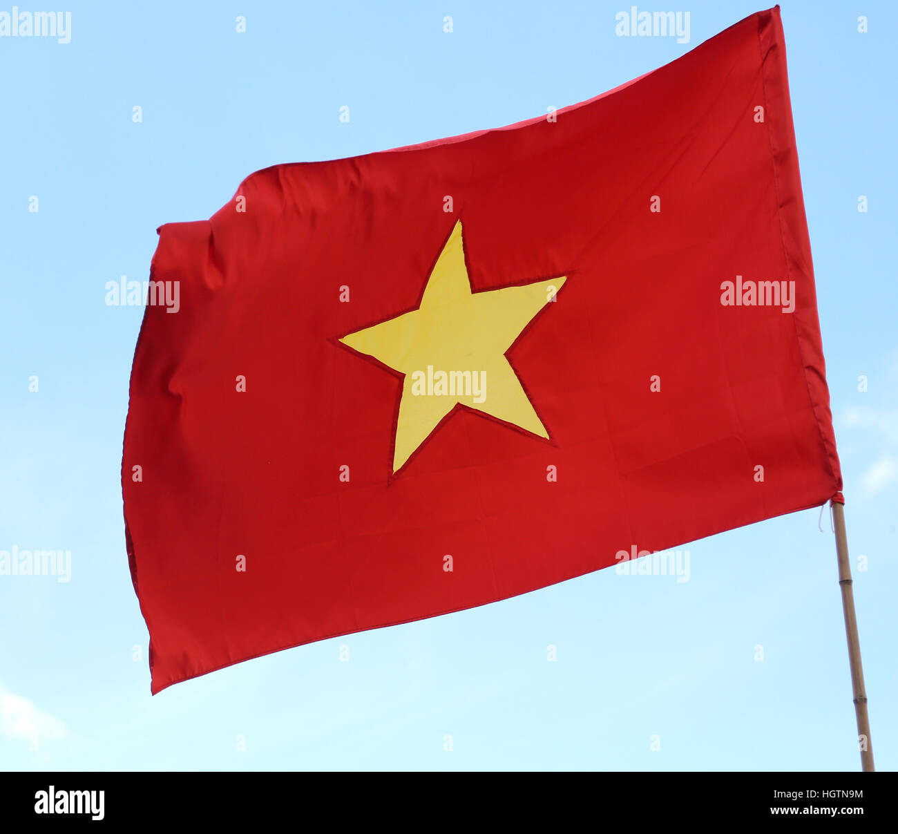 waving red flag of vietnam with the big yellow star waving stock