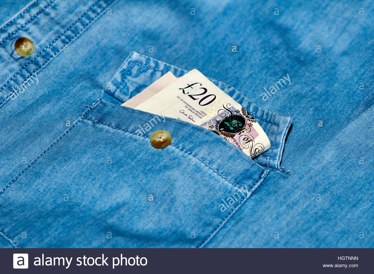 £20 pound notes in the top pocket of a blue denim shirt - Stock Image