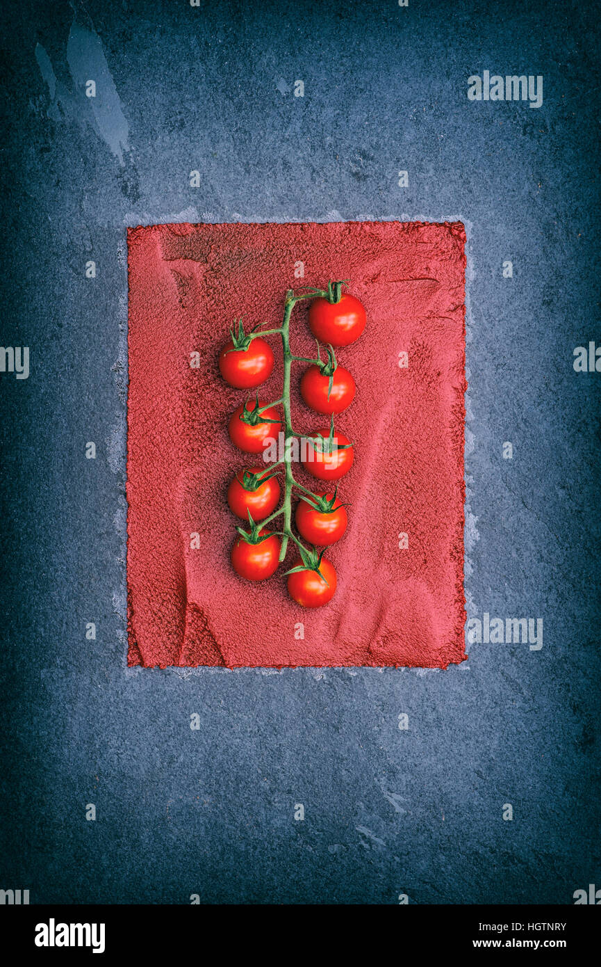 Vine tomatoes on tomato paste and slate. Retro filter applied - Stock Image