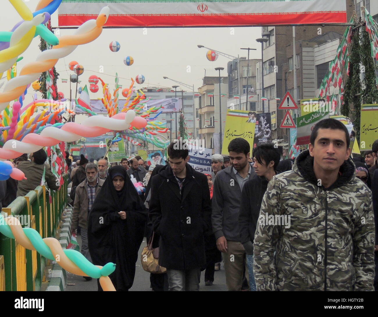 Iranian people march in Tehran streets at Islamic Revolution anniversary rally, national day of Iran - street level - Stock Image