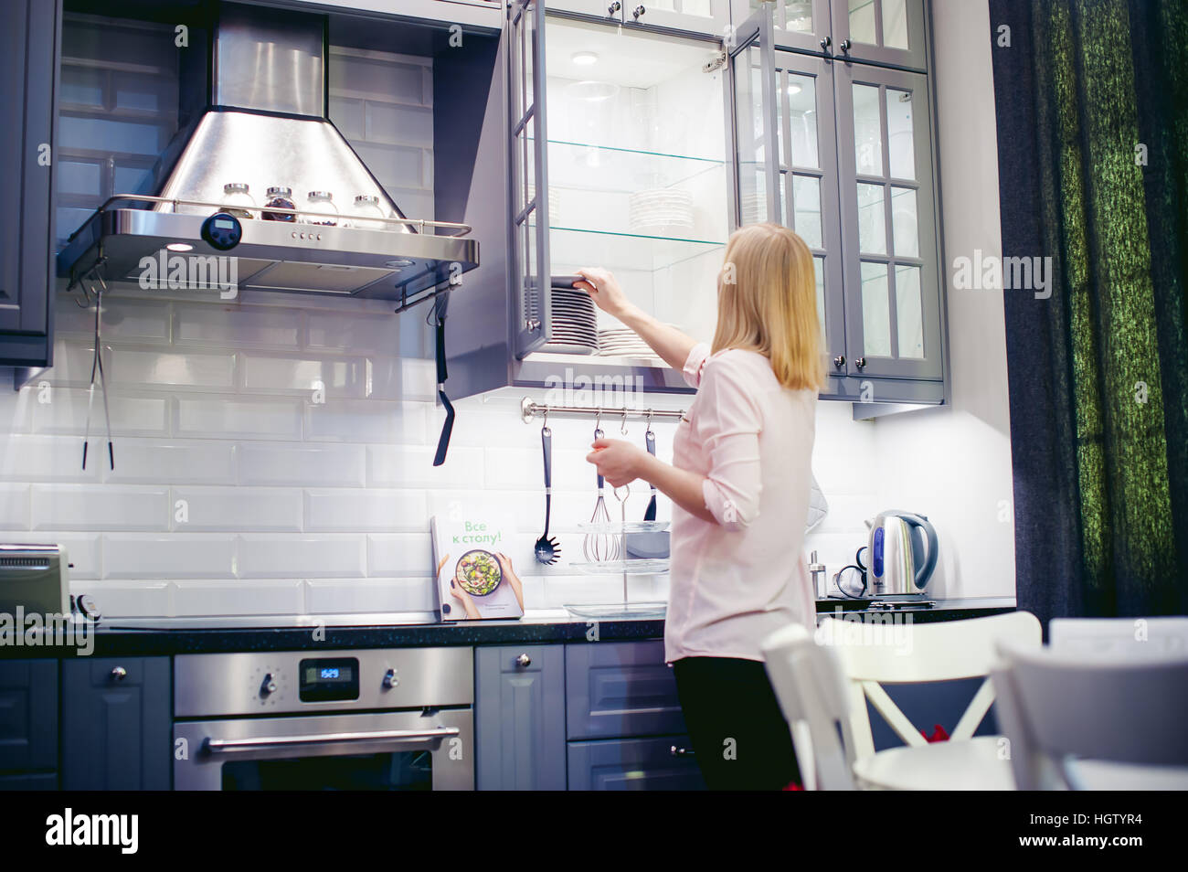 woman housewife in the kitchen. girl pulls out from the shelf cupboard dishes for table service. - Stock Image