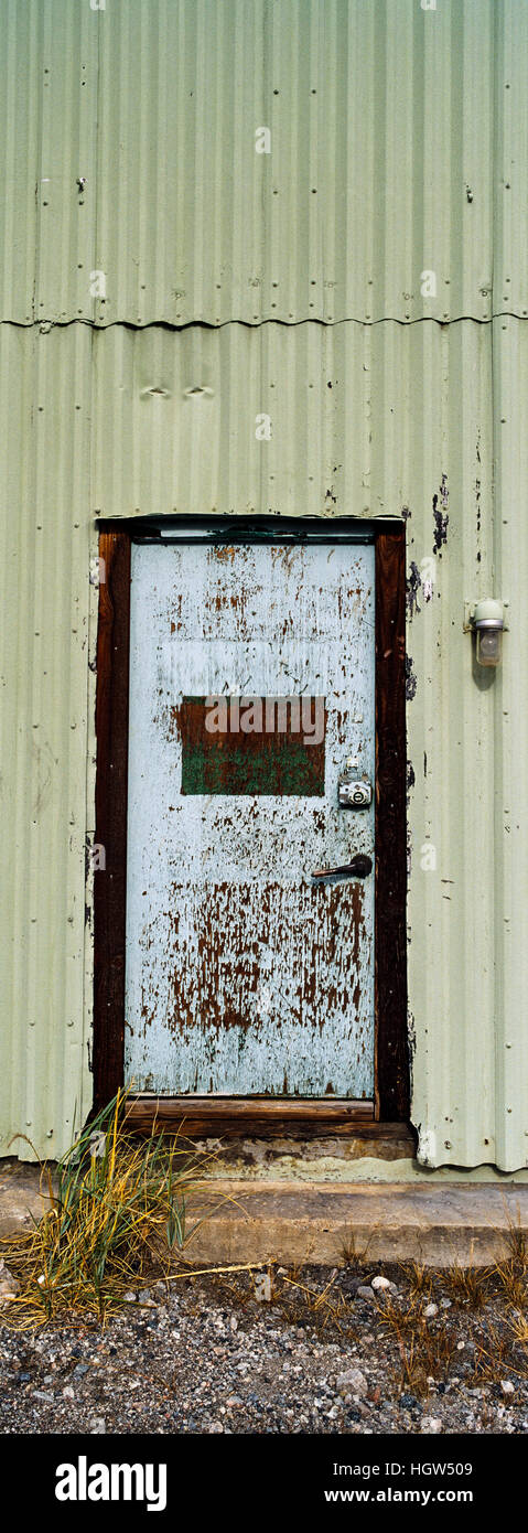 A corrugated tin wall and steel door in an old factory. - Stock Image